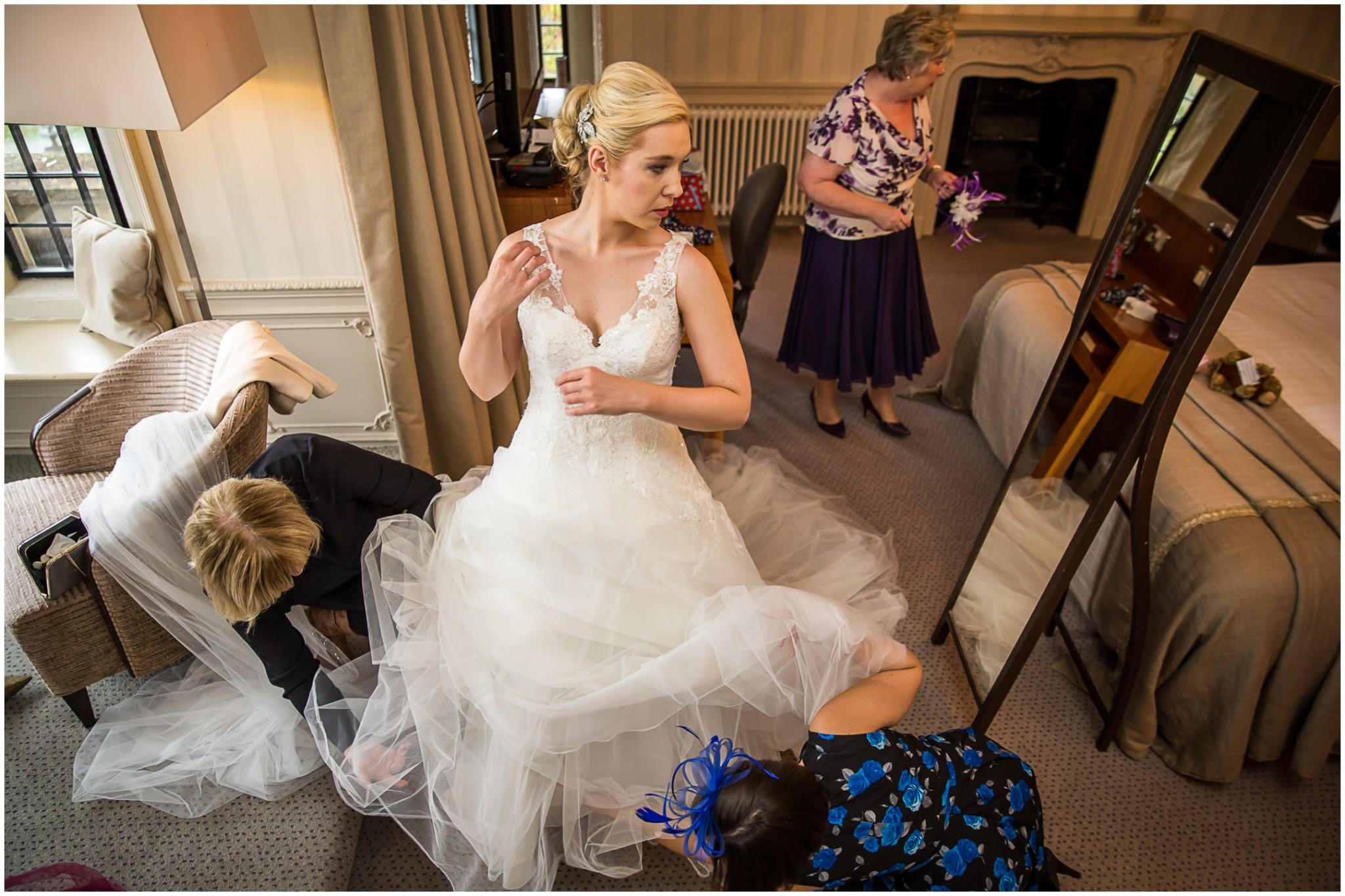 Rhinefield House Wedding Photographer Bride adjusting dress