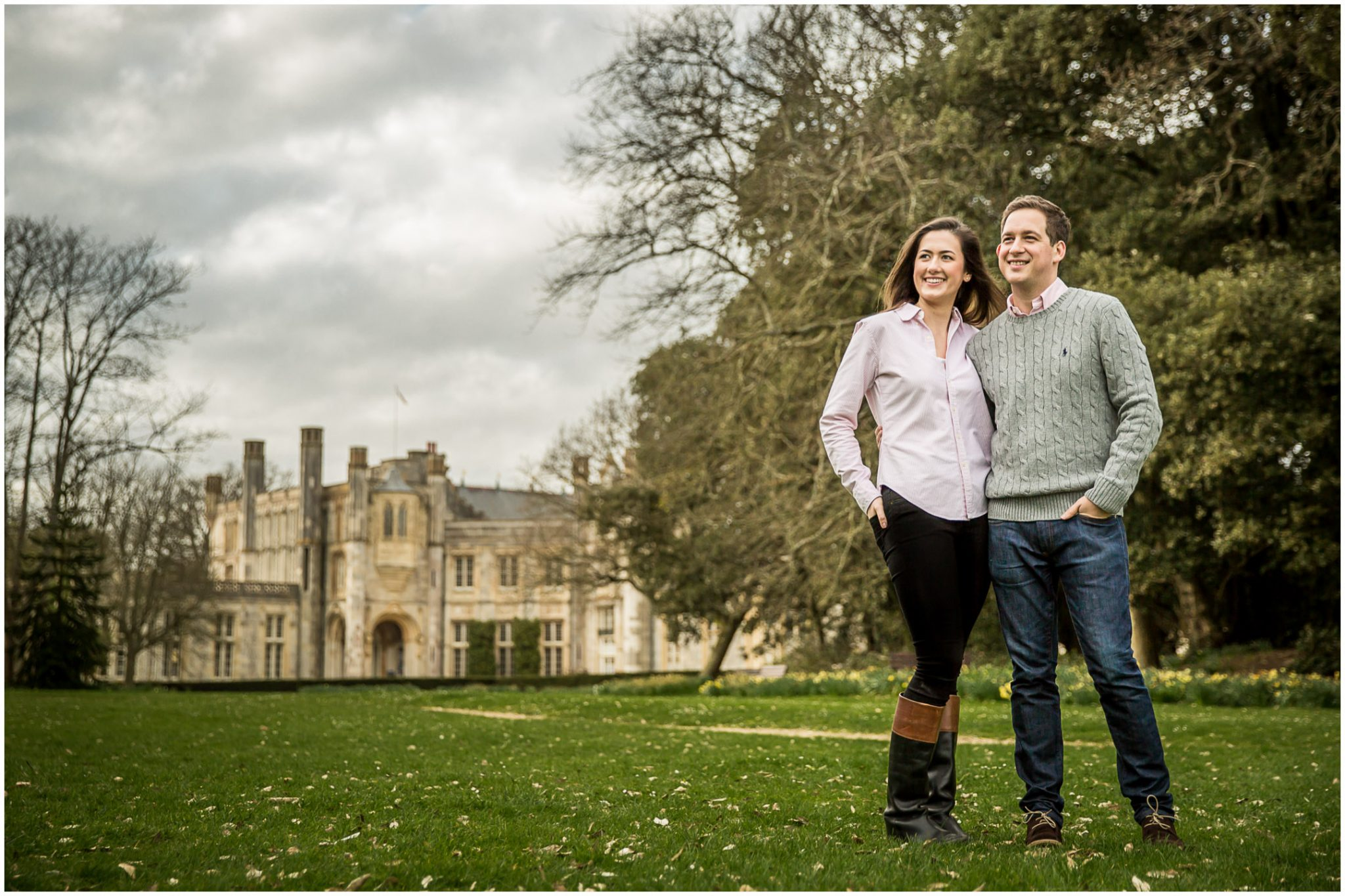 Couple stood in front of Highcliffe Castle in Hampshire as part of engagement photoshoot