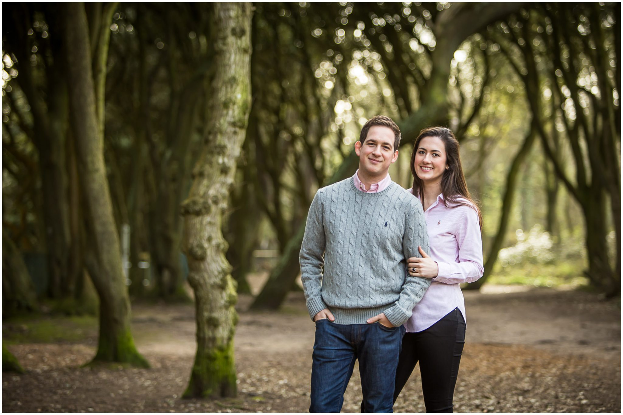 Bride and groom stood together amongst treest at Highcliffe Castle engagement shoot