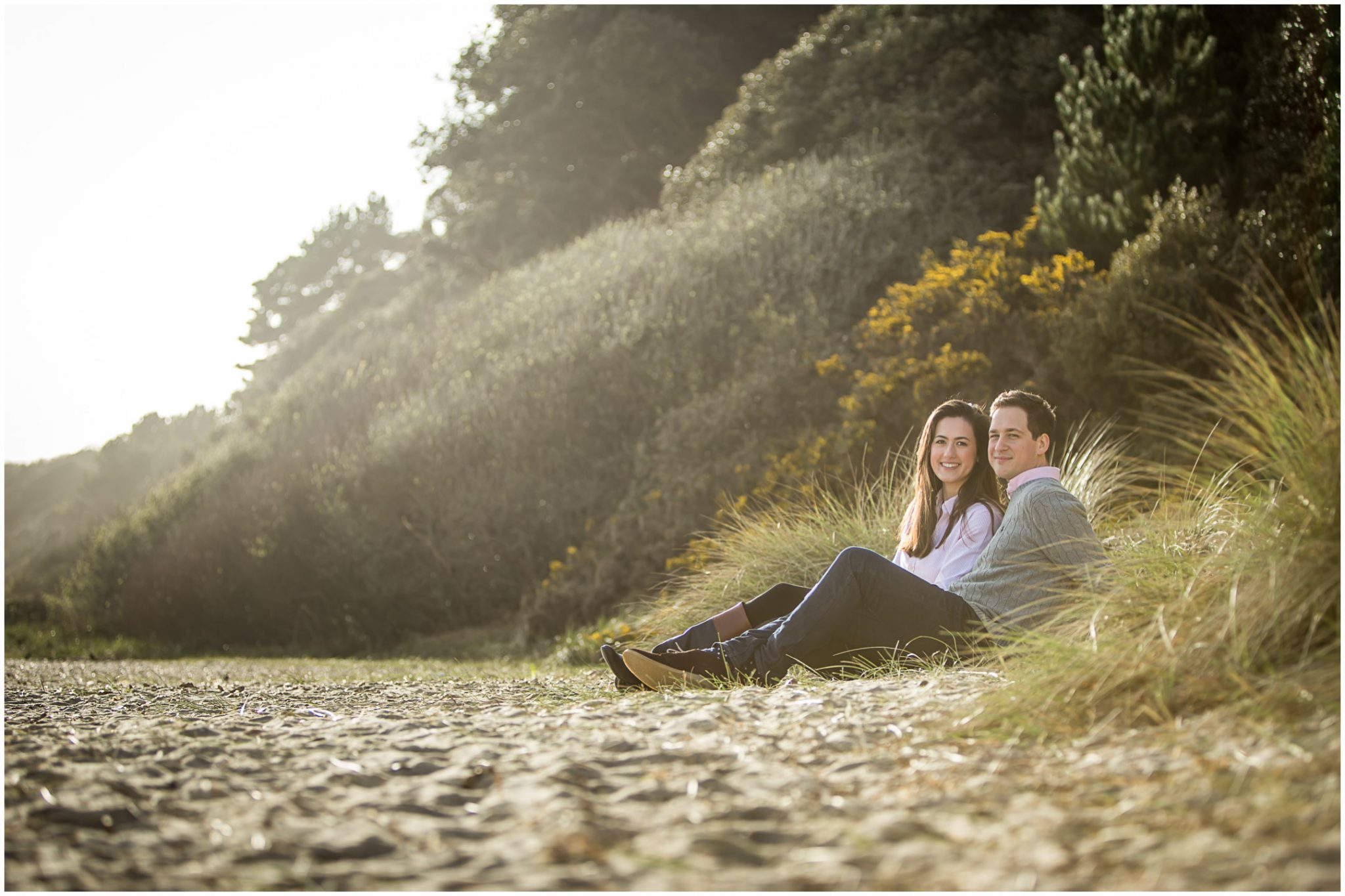 Bride and groom sat on sandy beach at Highcliffe in New Forest UK