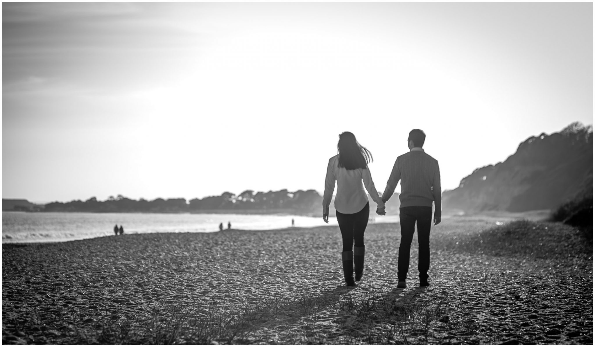 Black and white photo of bride and groom walking hand in hand along the beach towards the sun