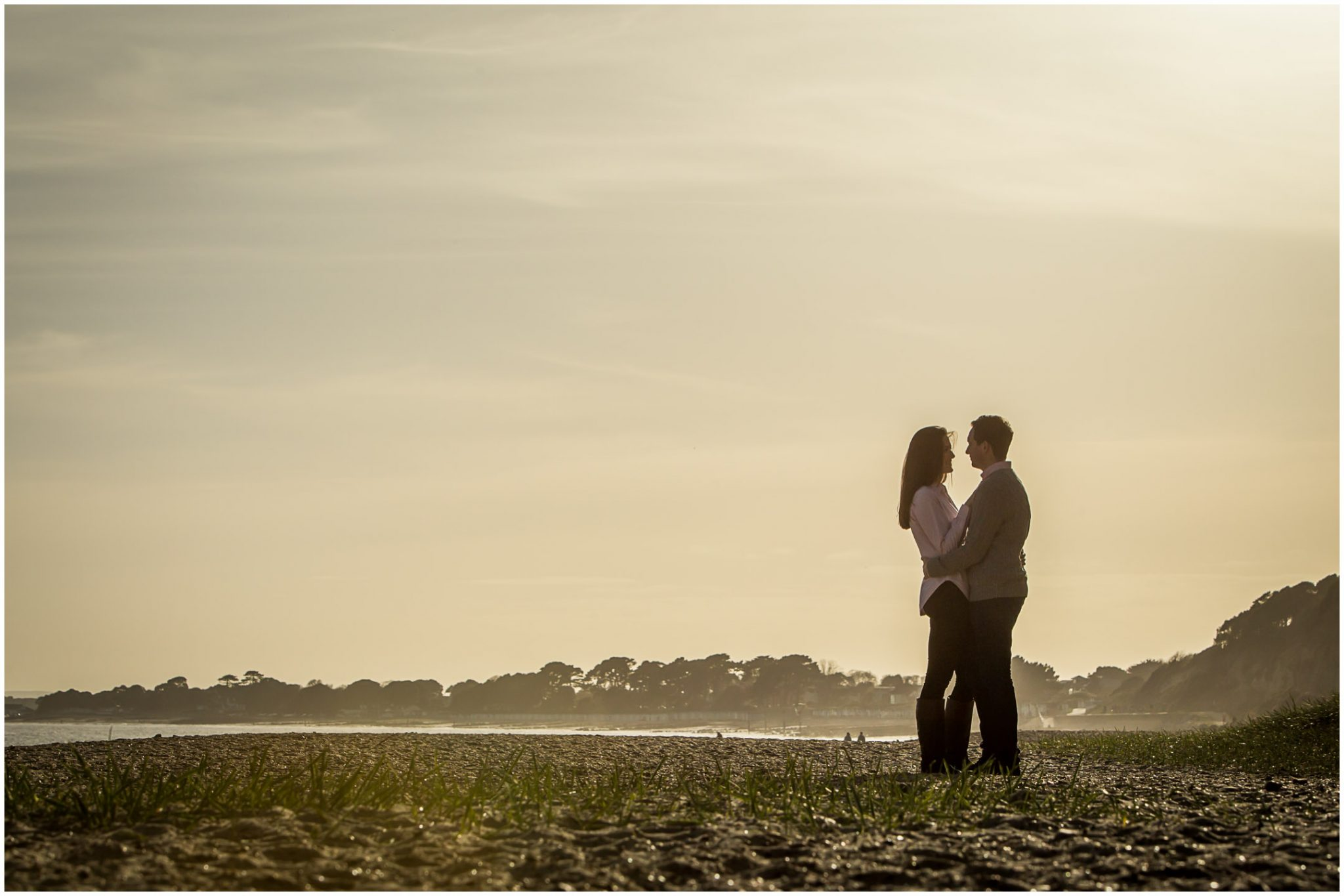 Couple stood facing each other on beach in Hampshire in evening light