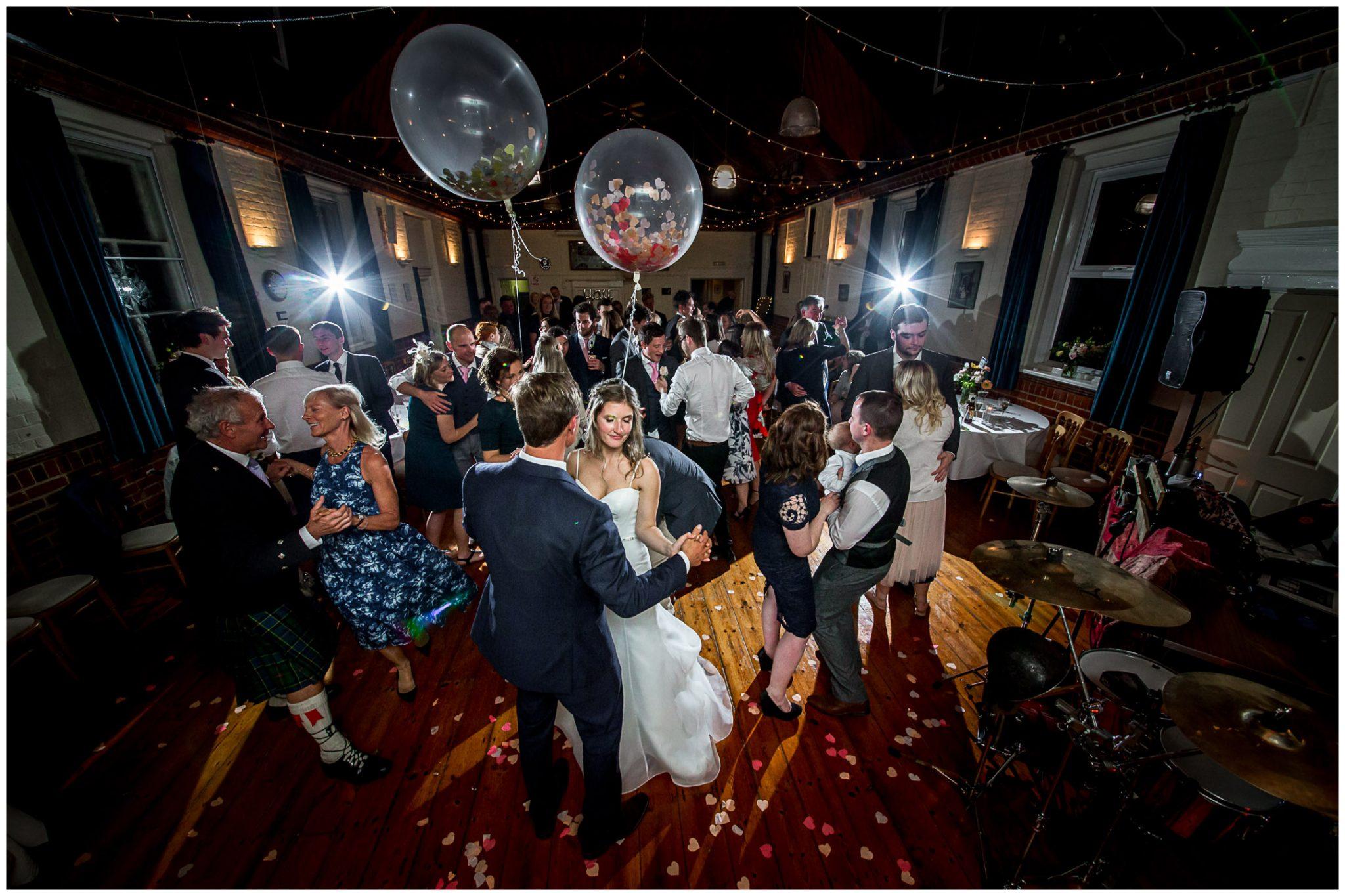 Bride, groom and guests dancing at village hall wedding reception