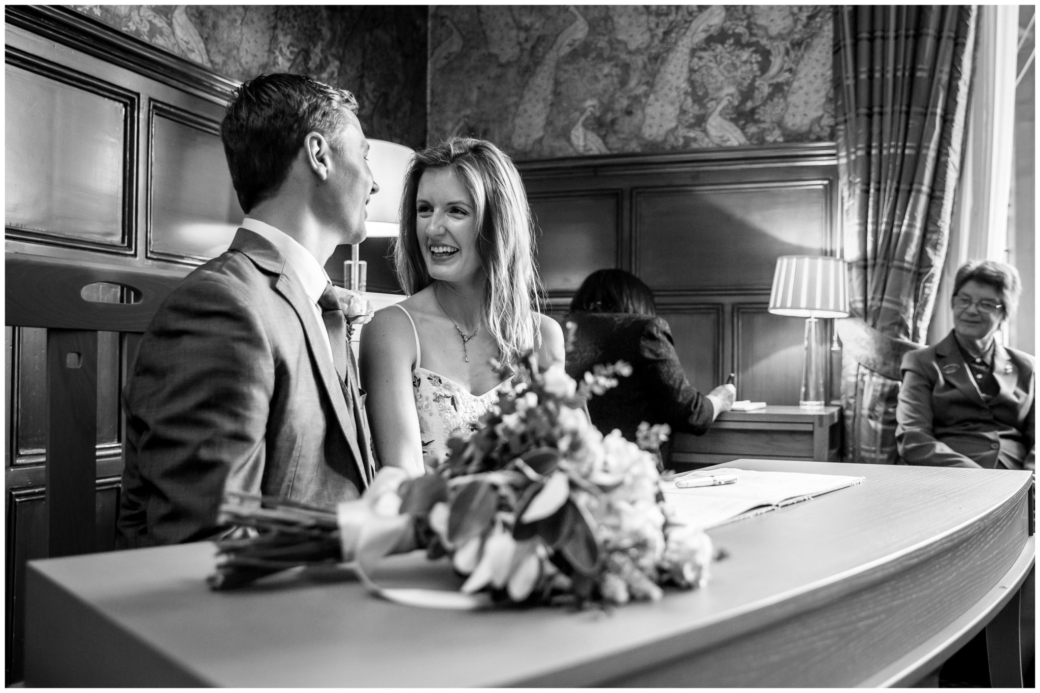 Bride and groom laugh at table while register is signed