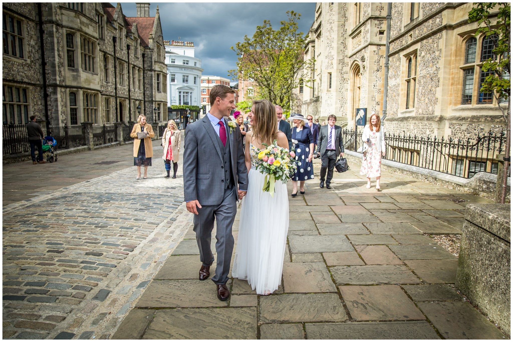 Couple walk along Winchester Castle Avenue after wedding