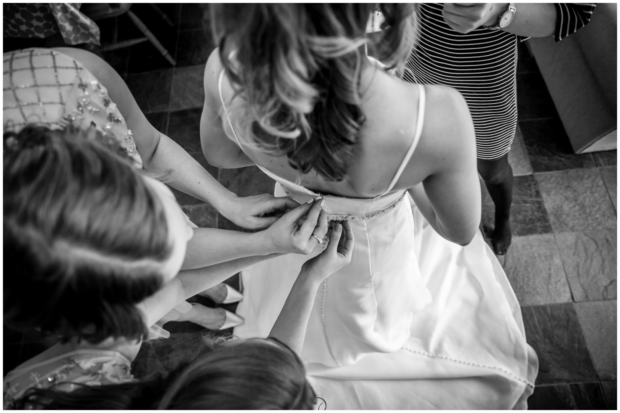 Black and white image of bridesmaids buttoning up bride's dress