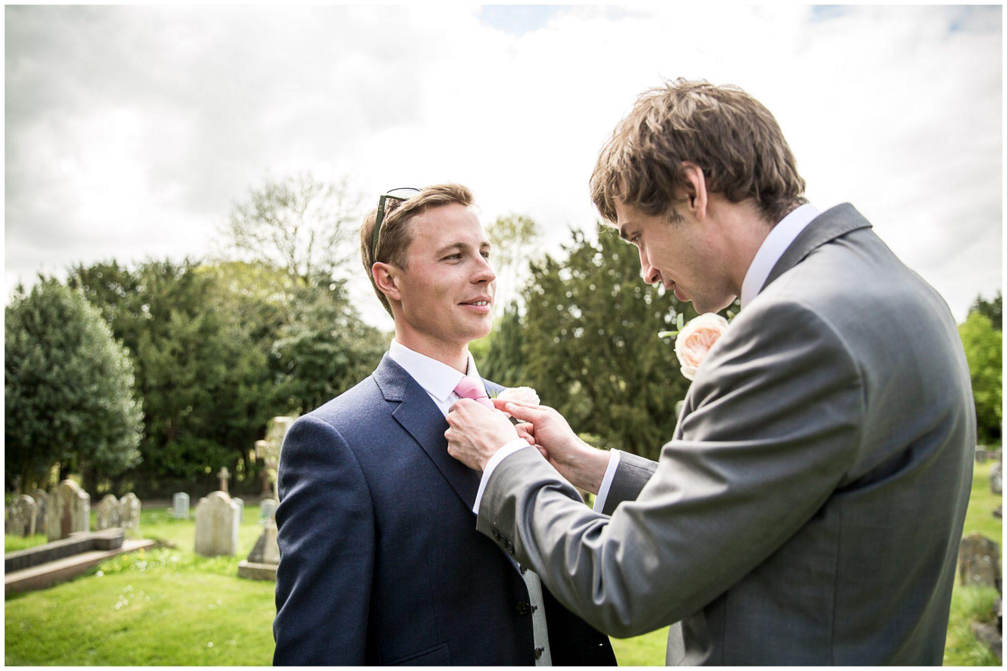 Best man arranges groom's tie outside Twyford Church before marriage begins