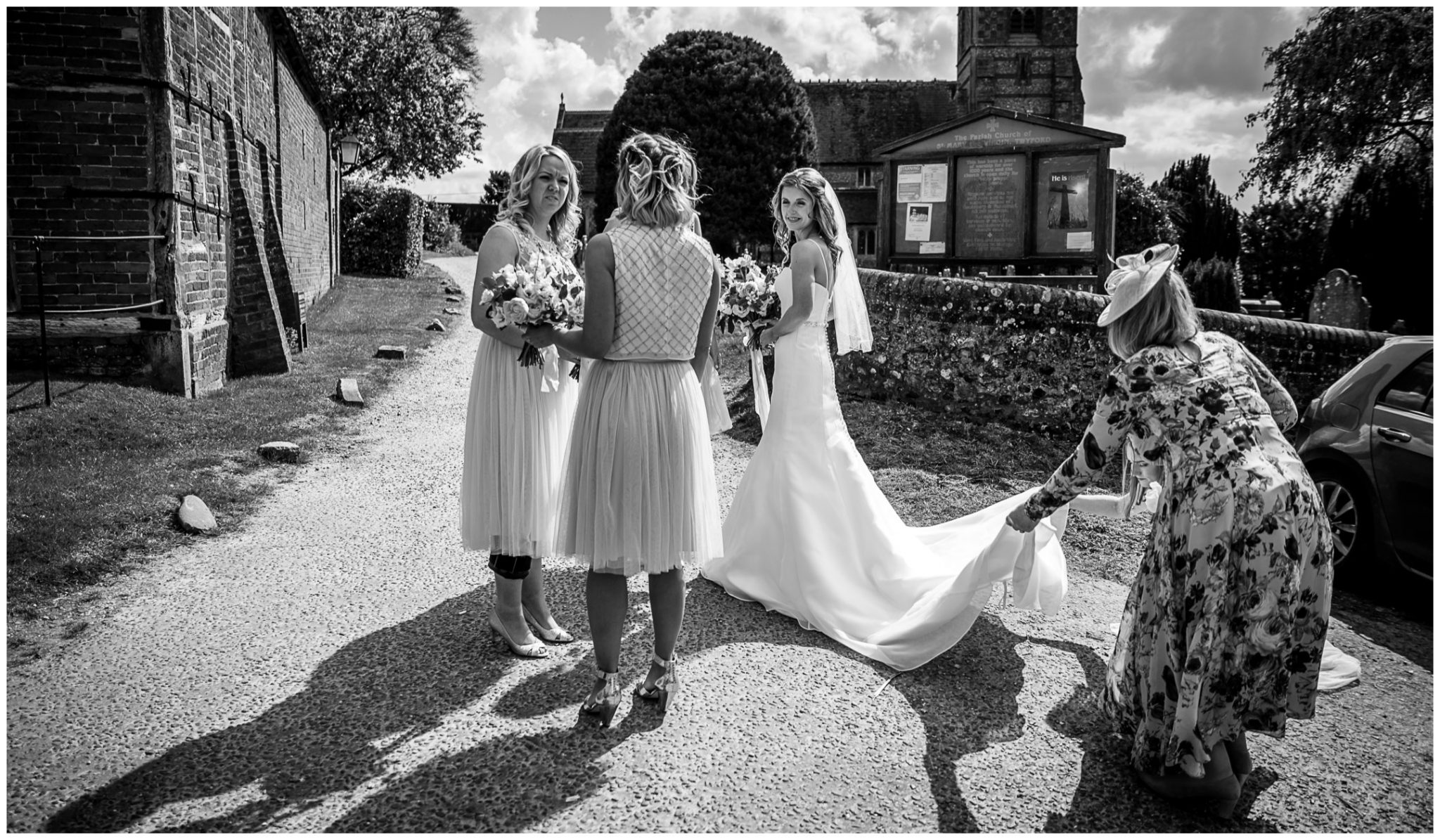 Bride's mother arranges bride's dress before start of wedding at Twyford Church of St Mary's