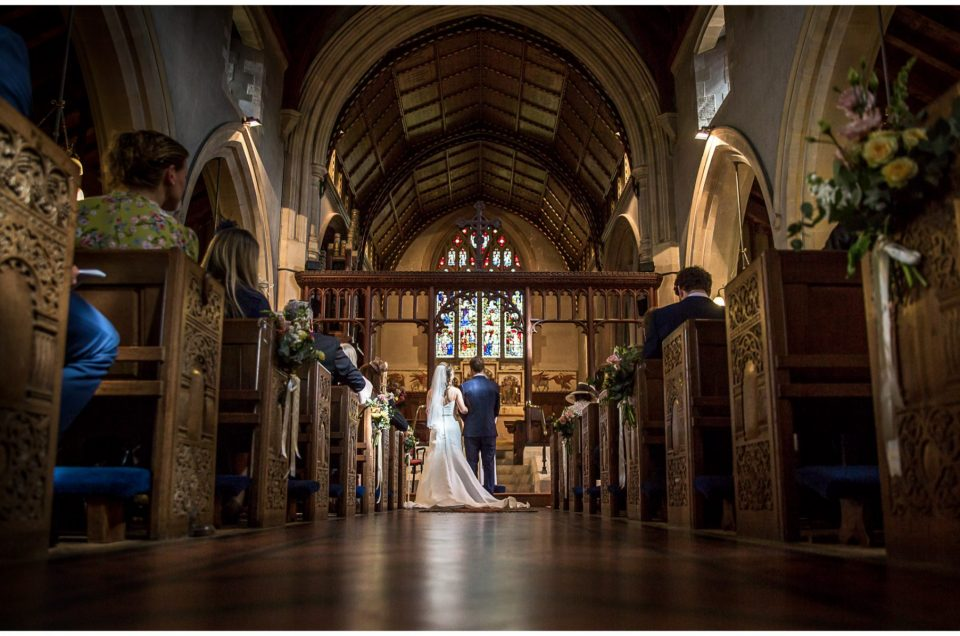 Colour photo of bride and groom stood at the end of the aisle