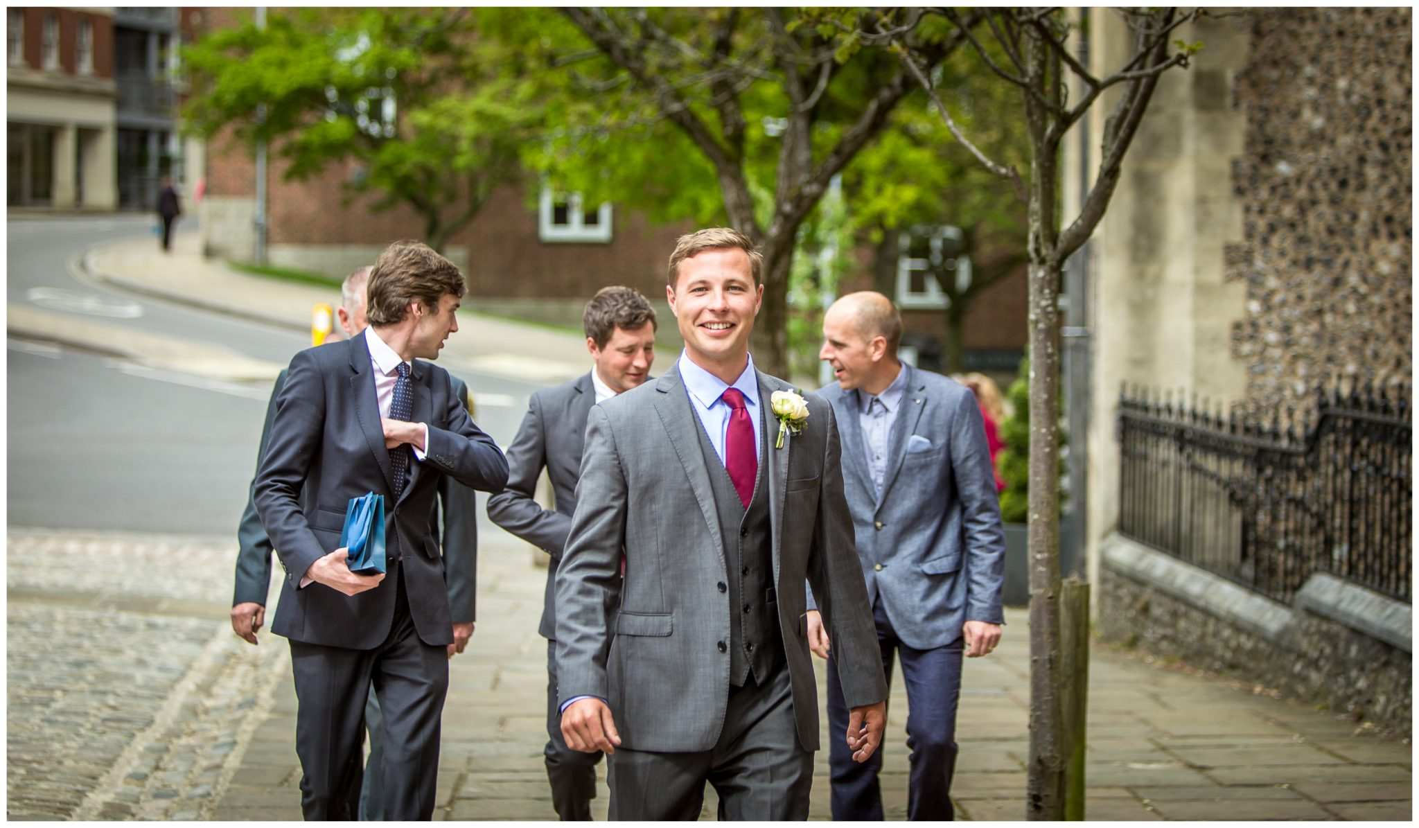 Groom and groomsmen walk towards registry office in Winchester