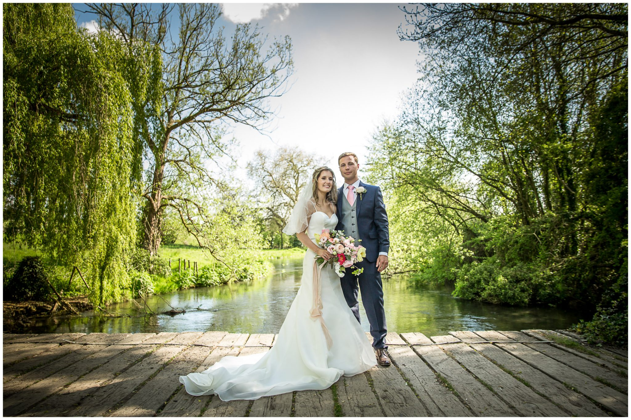 Colour portrait of bride and groom in summer shade by river