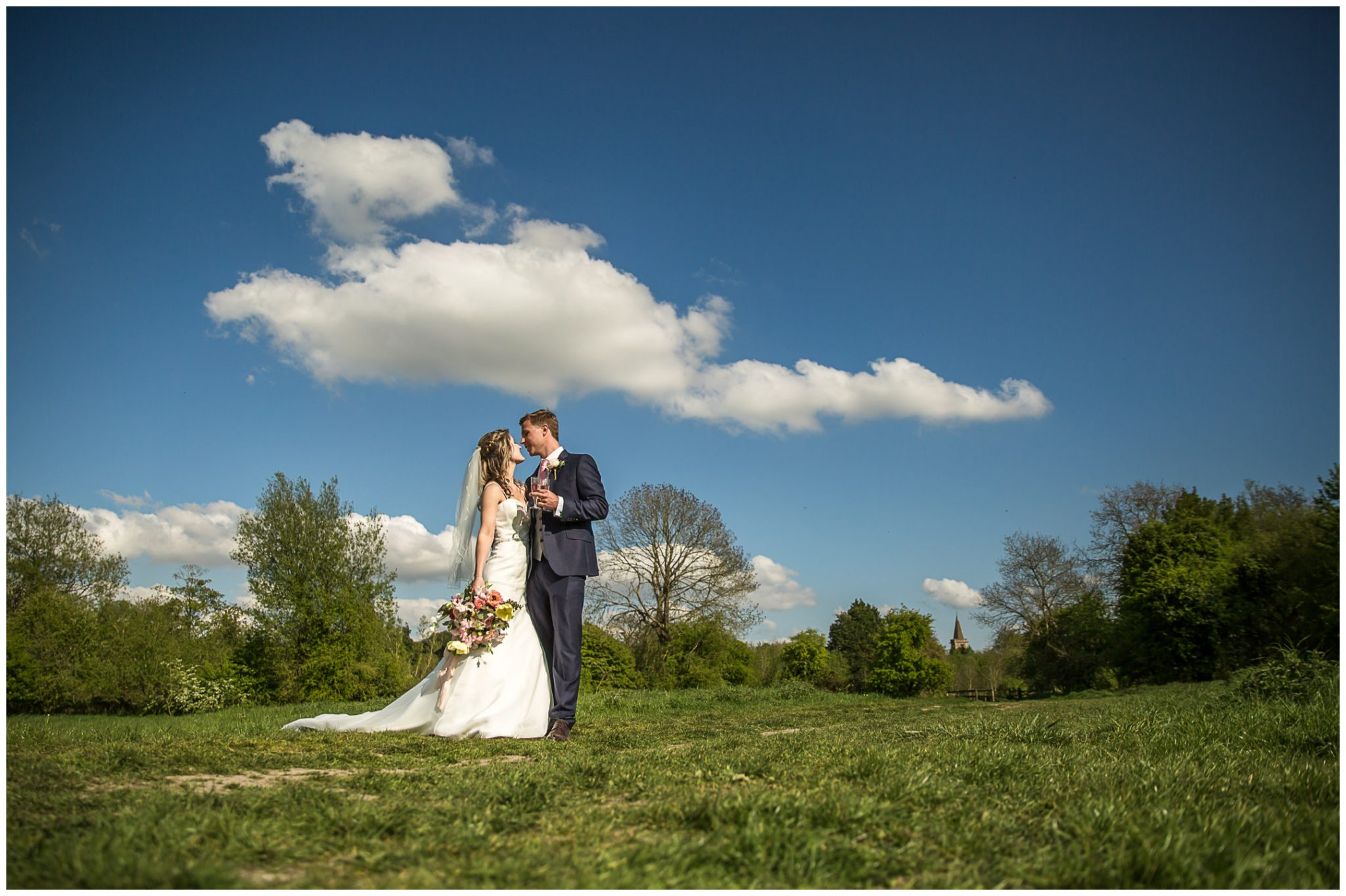 Wedding couple stood in Twyford water meadows with St Marys church in background