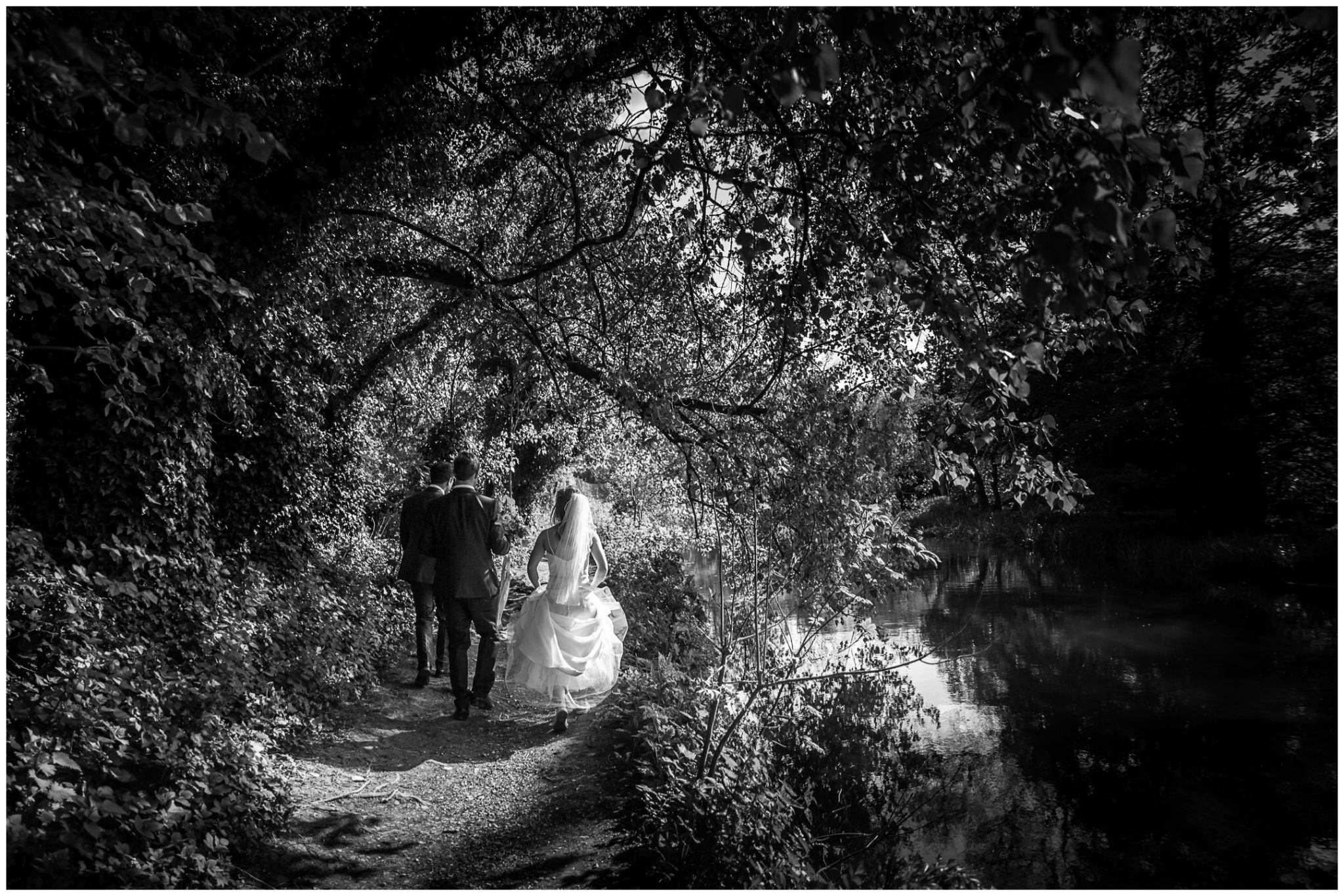 Black and white photo of wedding couple walking beside river