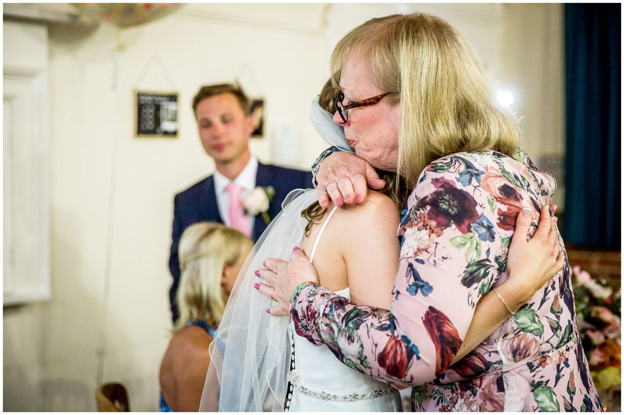 Mother of the bride hugs her daughter after giving a wedding speech