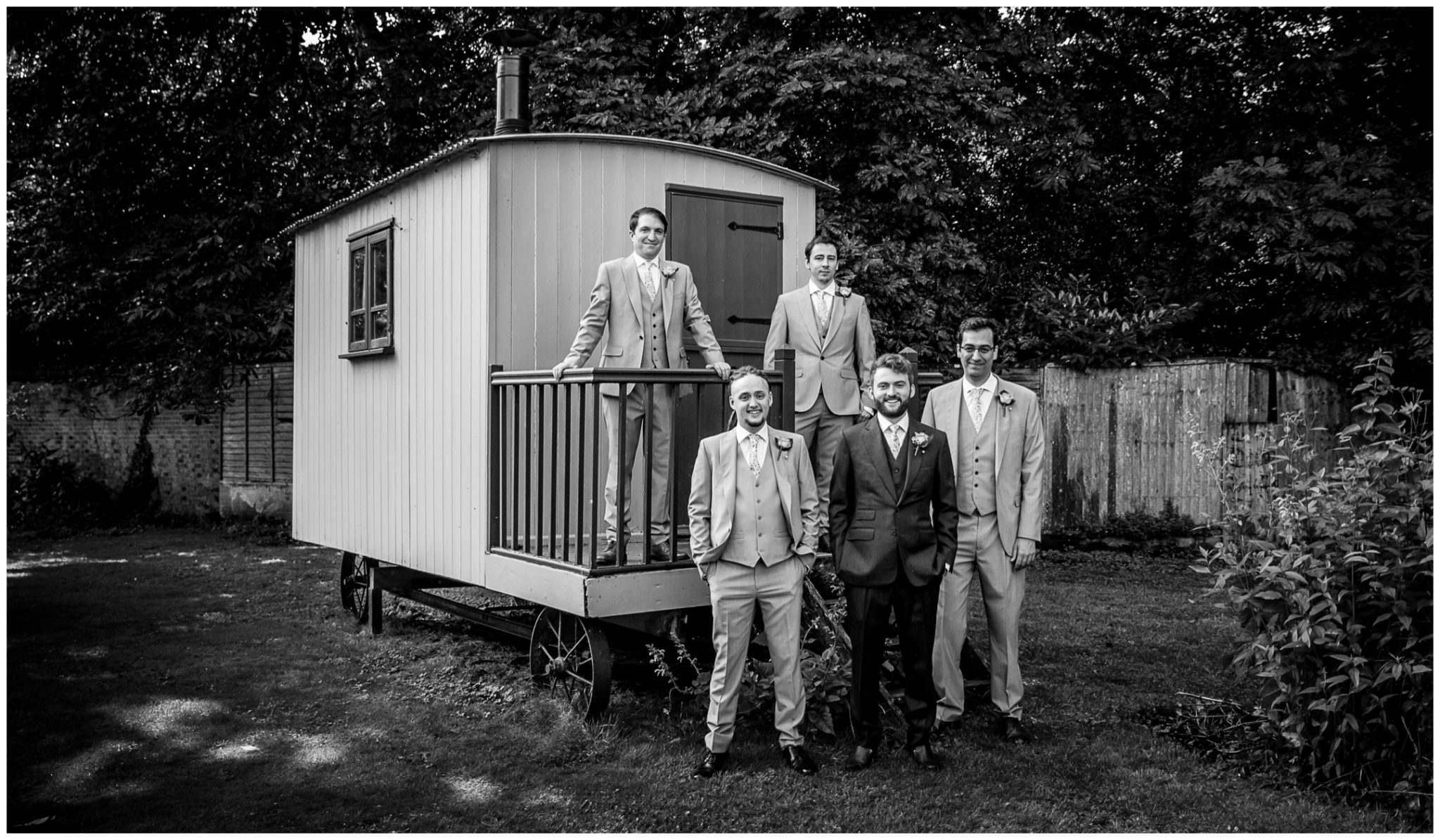 Groom, best man and groomsmen stand by shepherds hut at Deans Court Wimborne wedding venue