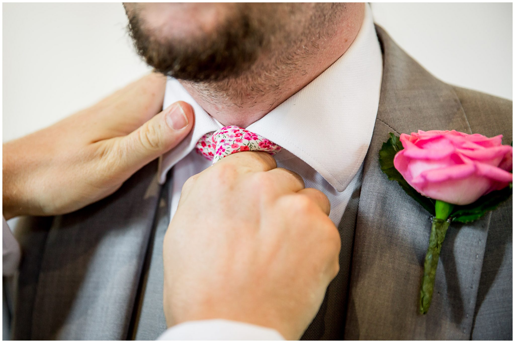 The best man adjusts the groom's tie before the marriage ceremony begins