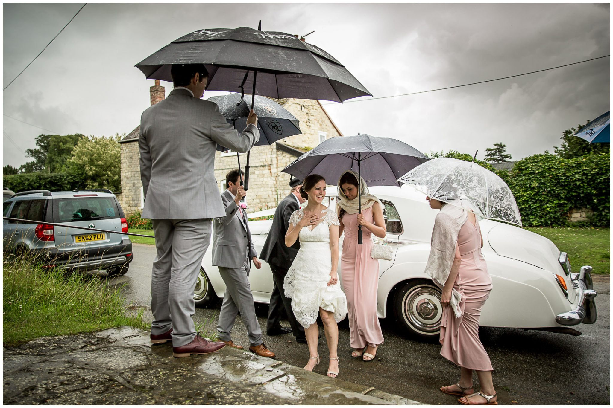 The bride steps out of the car sheltered by a canopy of umbrellas
