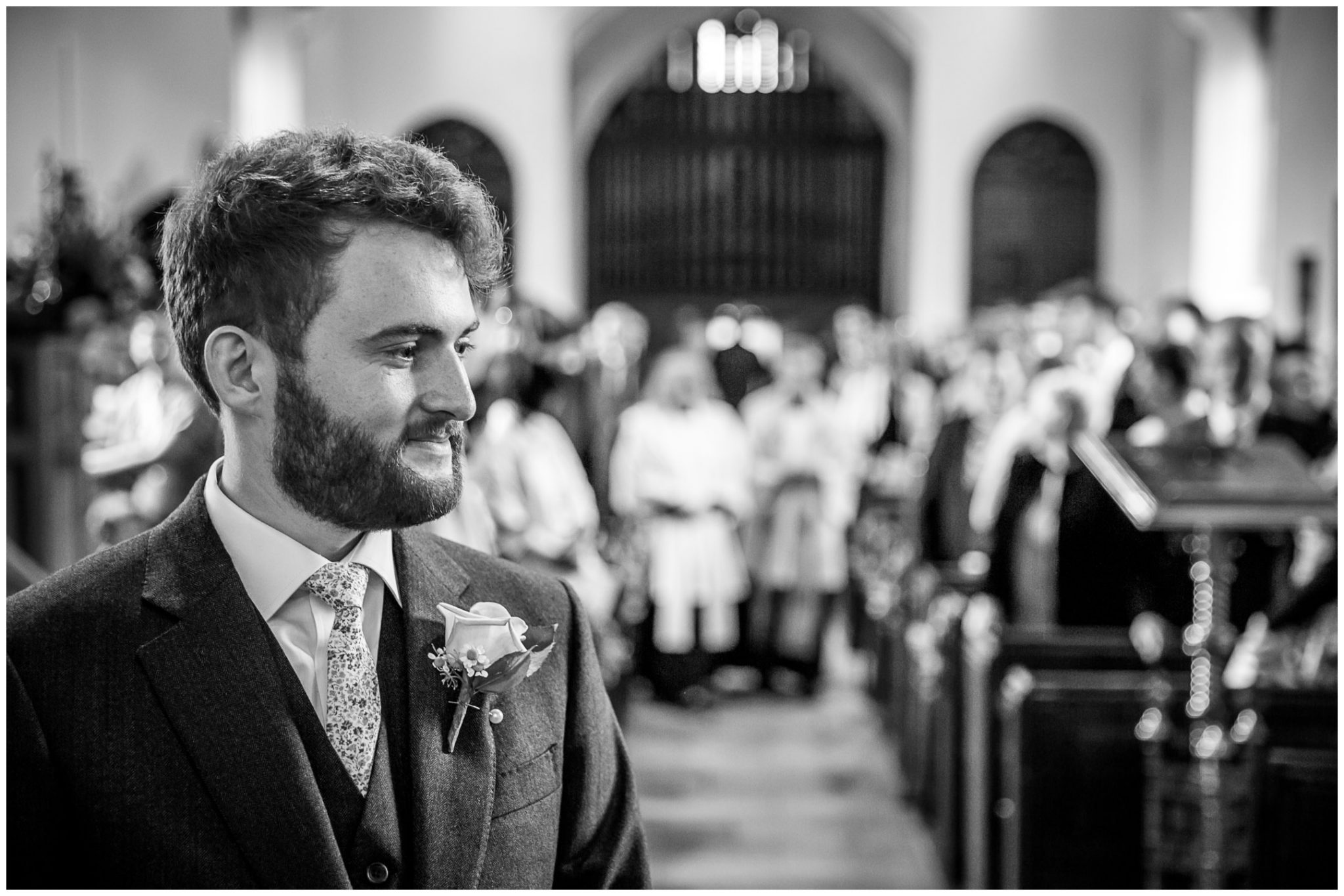 The groom anticipates the arrival of his bride as she walks down the aisle