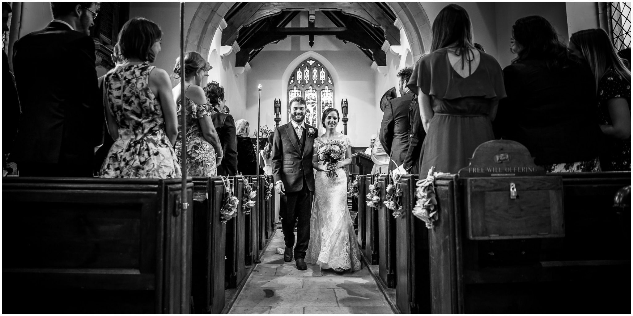 The newly married bride and groom walk down the aisle together as husband and wife