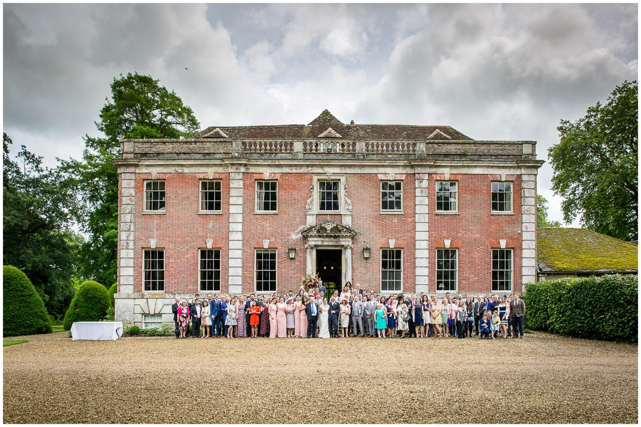 Full group photo of wedding guests outside Deans Court Dorset wedding venue