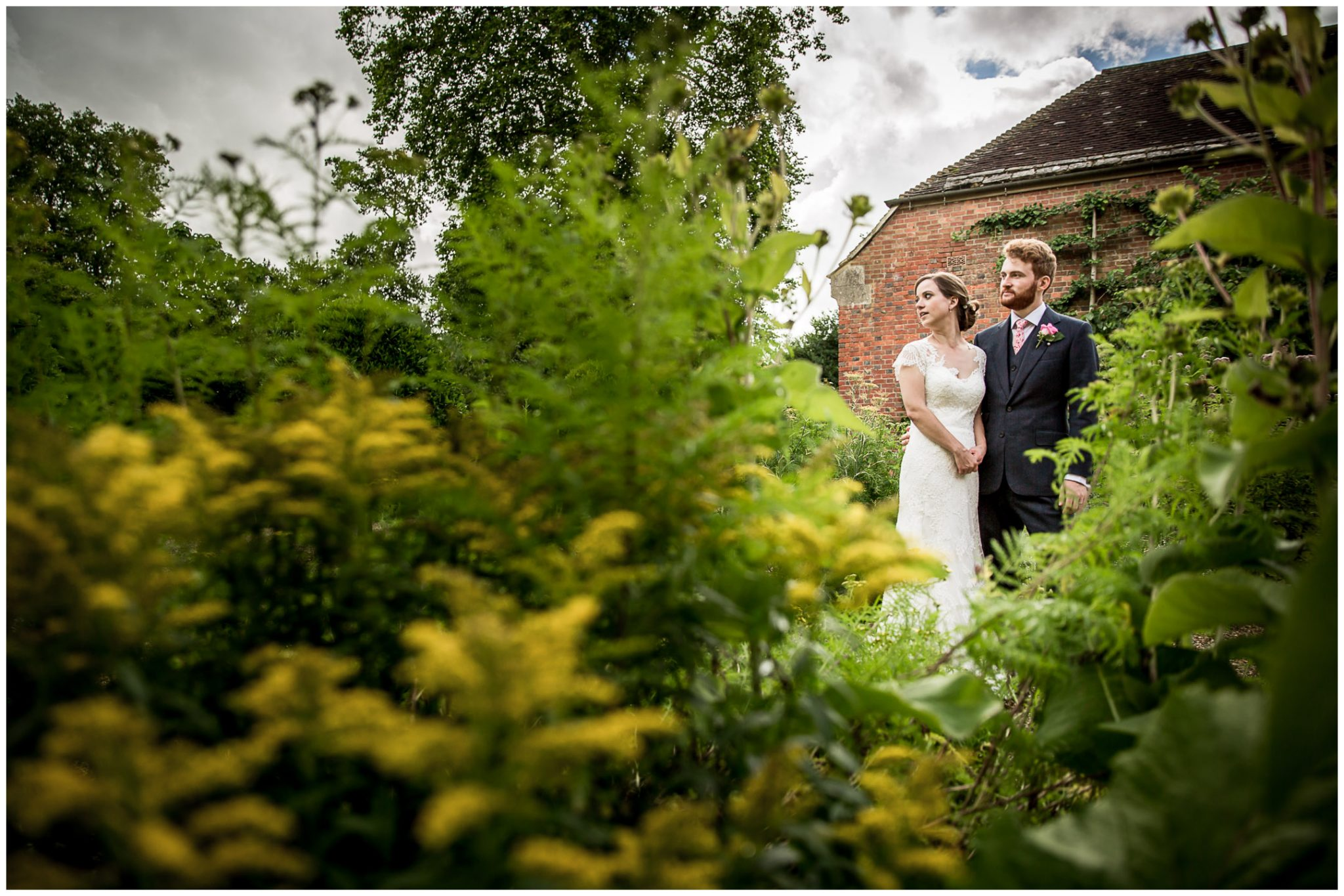 Couple amongst flowers in formal gardens at Deans Court