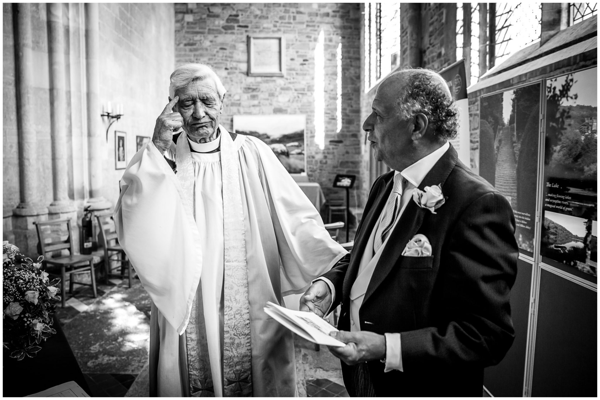 Candid moment with vicar and father of groom