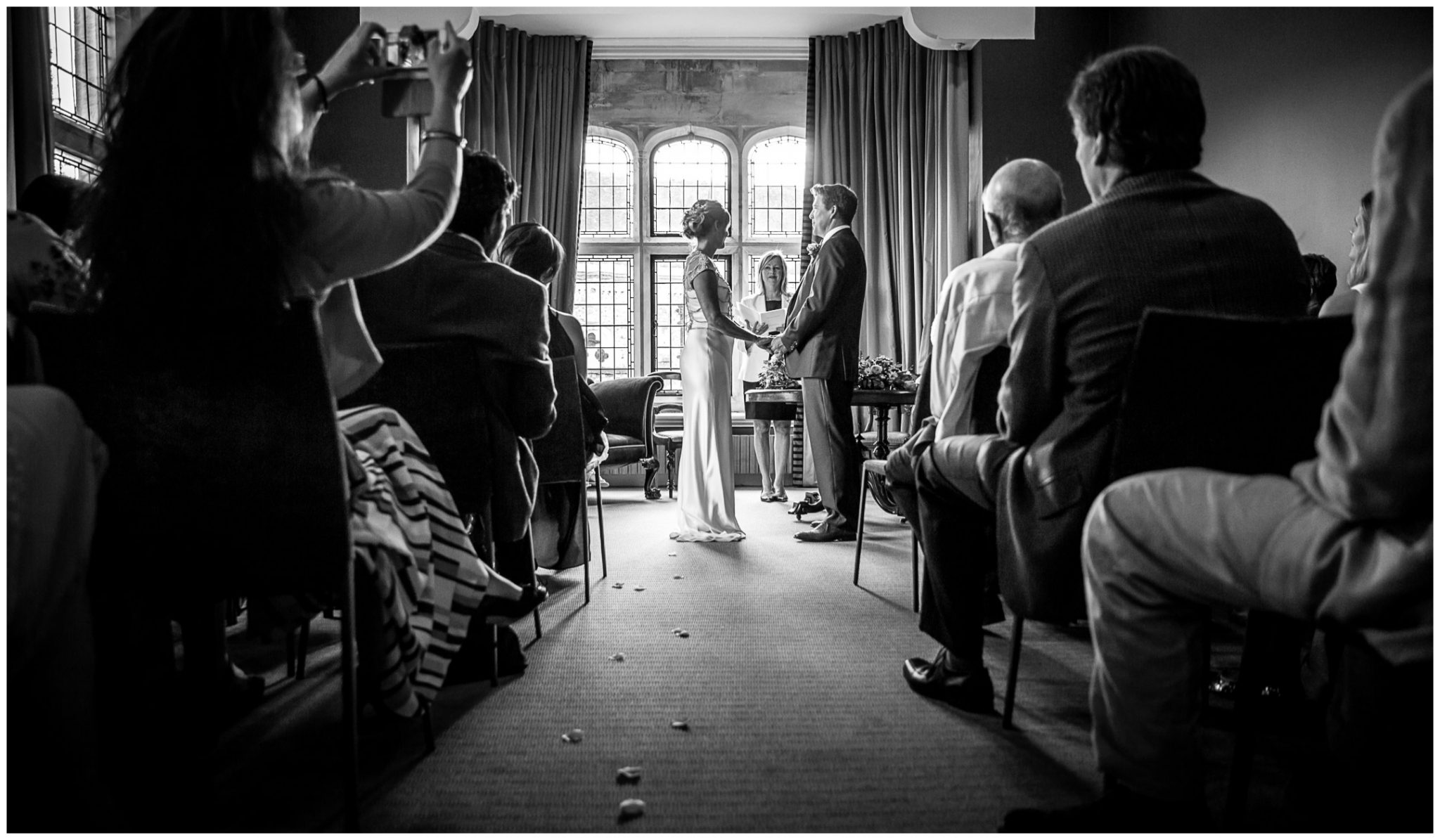Black and white photo of couple during the wedding taken from the rear of the Castle Room