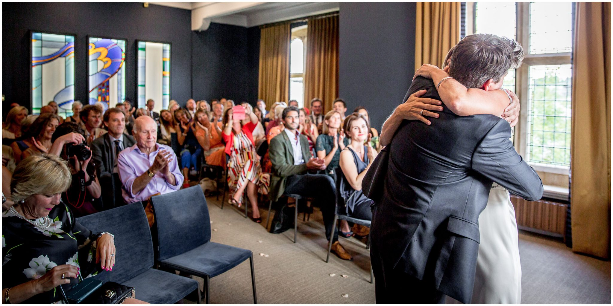 The newly married couple hug as their wedding guests applaud