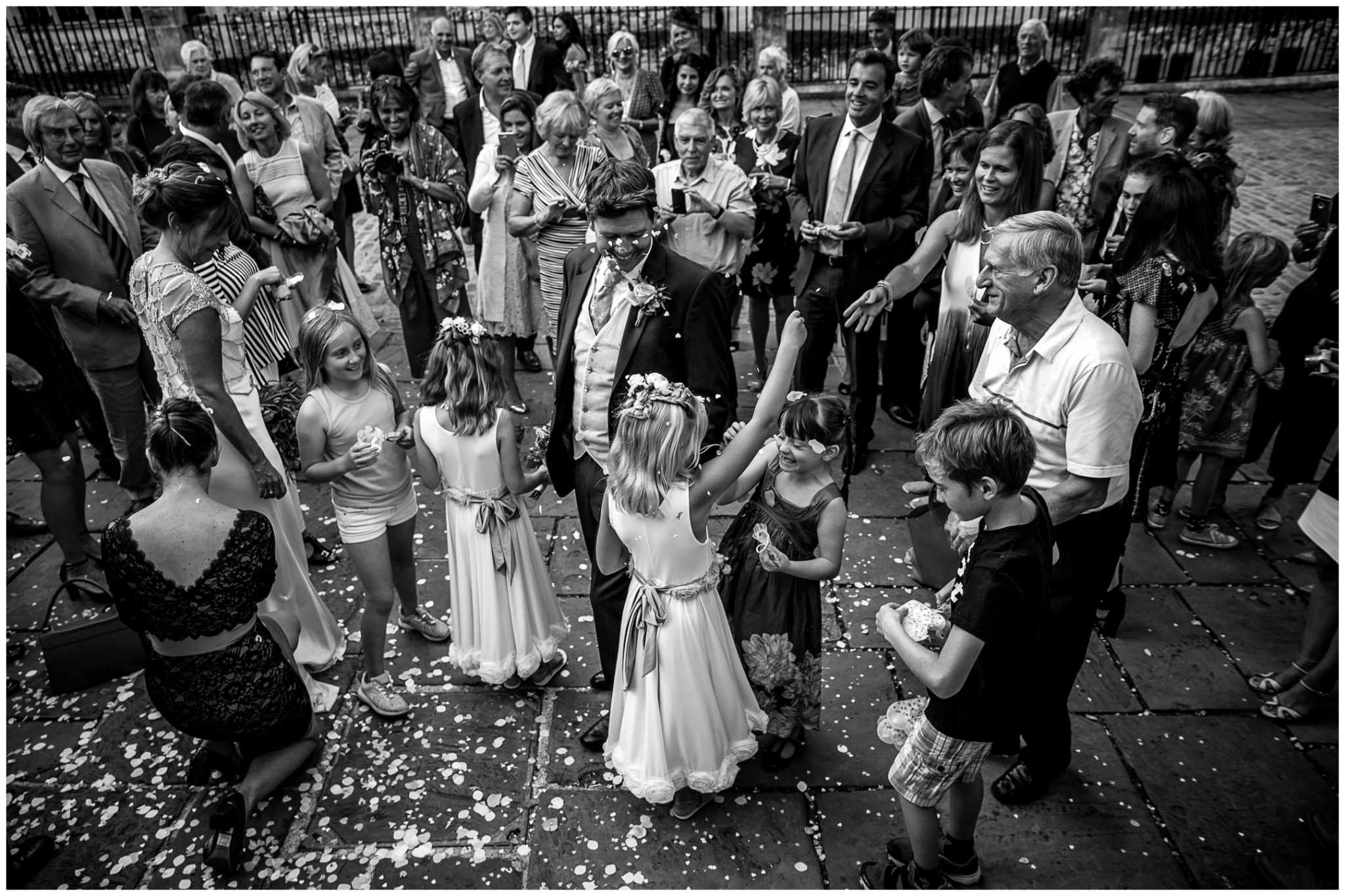 Black and white photo of guests throwing confetti outside registry office