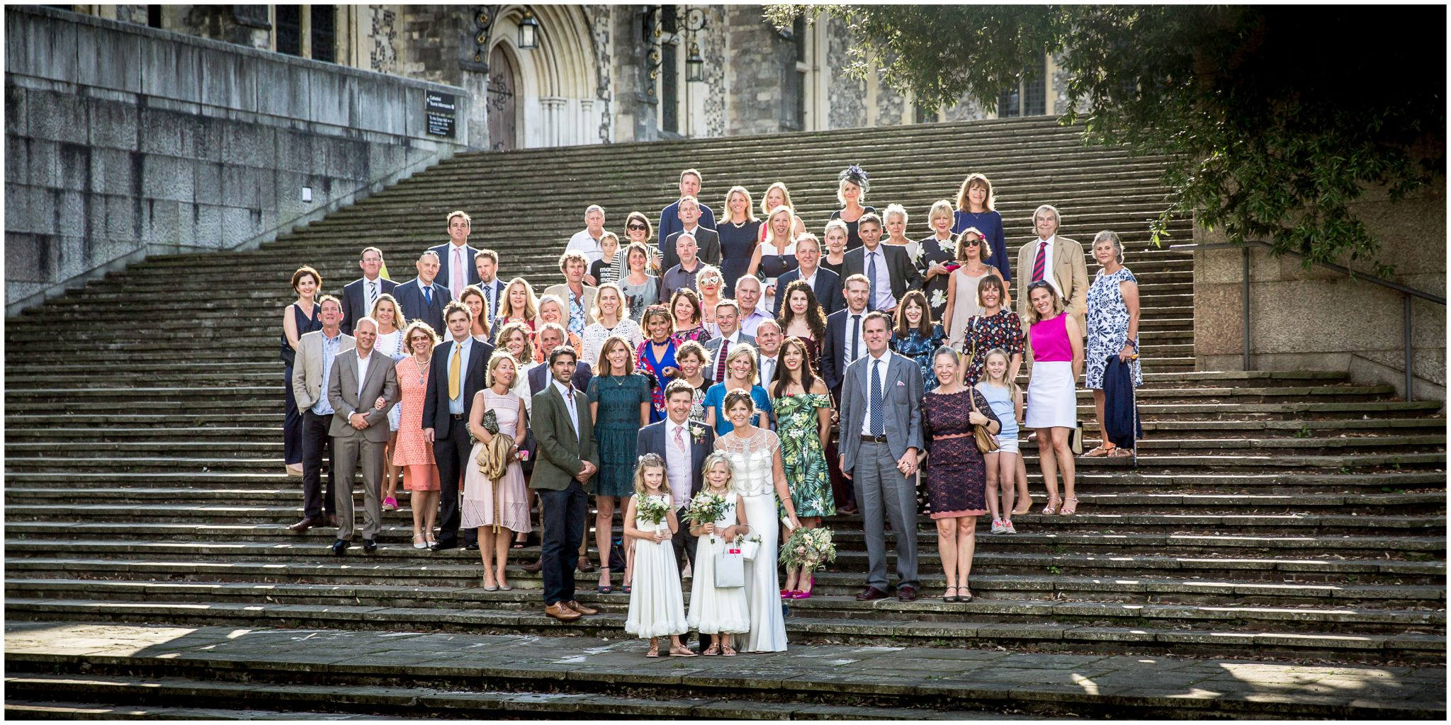 Group photo of all wedding guests stood on the steps outside Winchester Law Courts