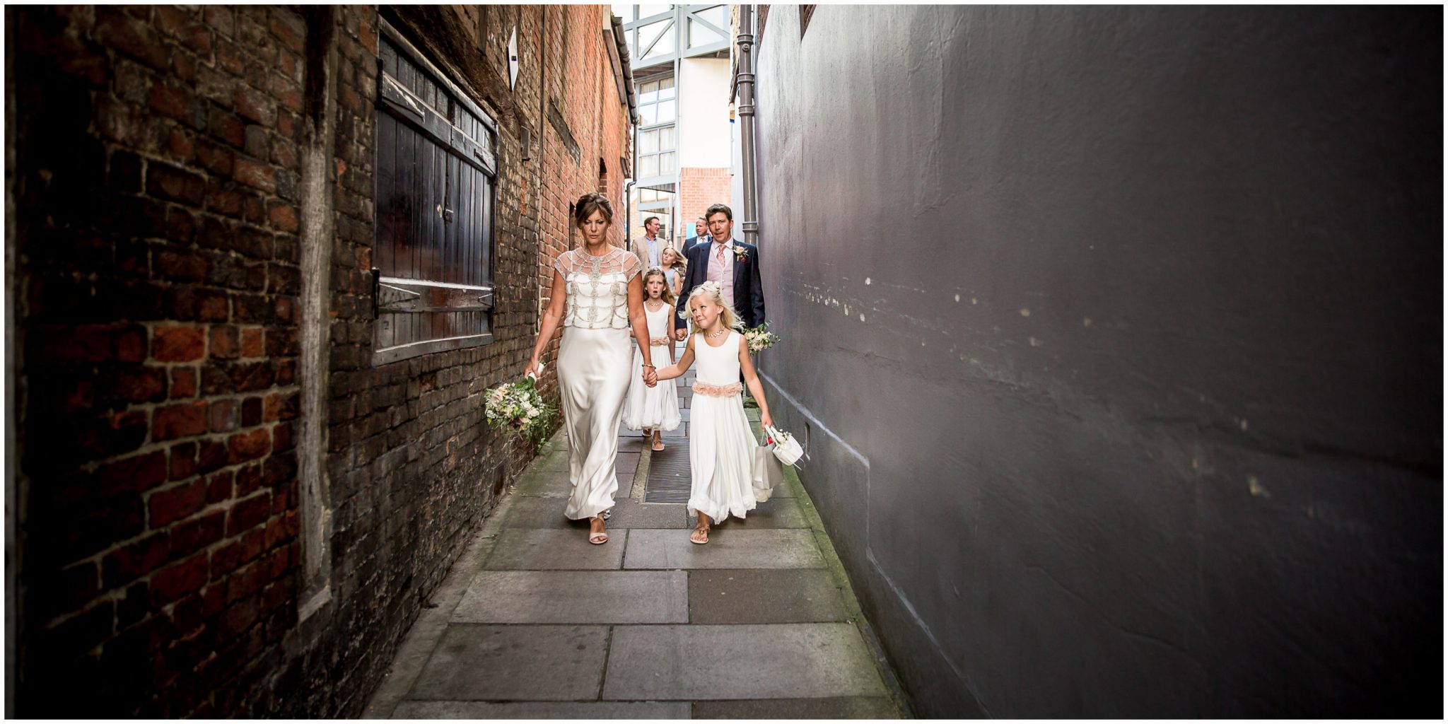 Bride, groom and flower girls walking through town