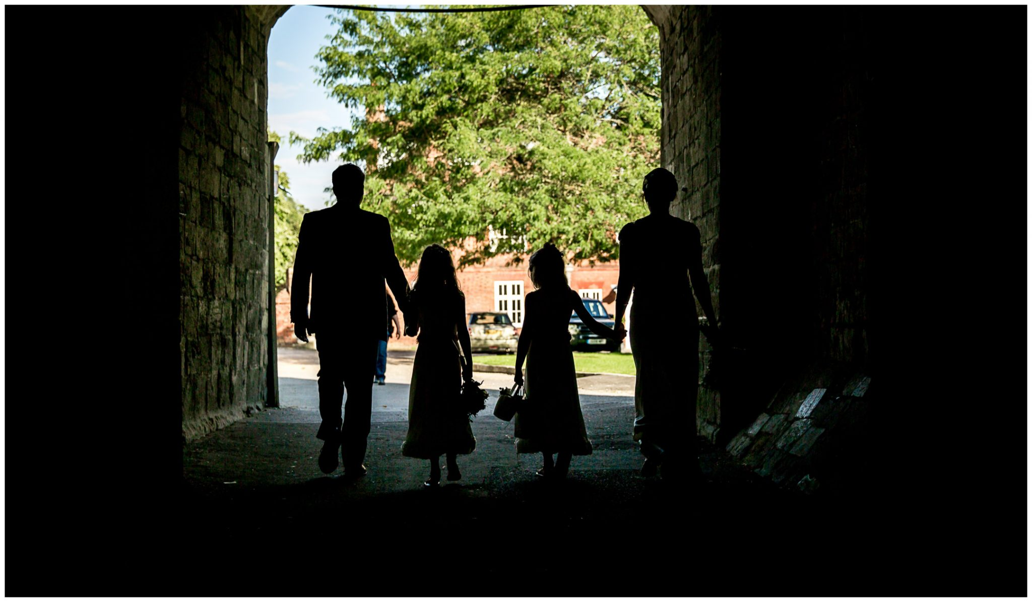 Bride, groom and their daughters walk through the Cathedral arch