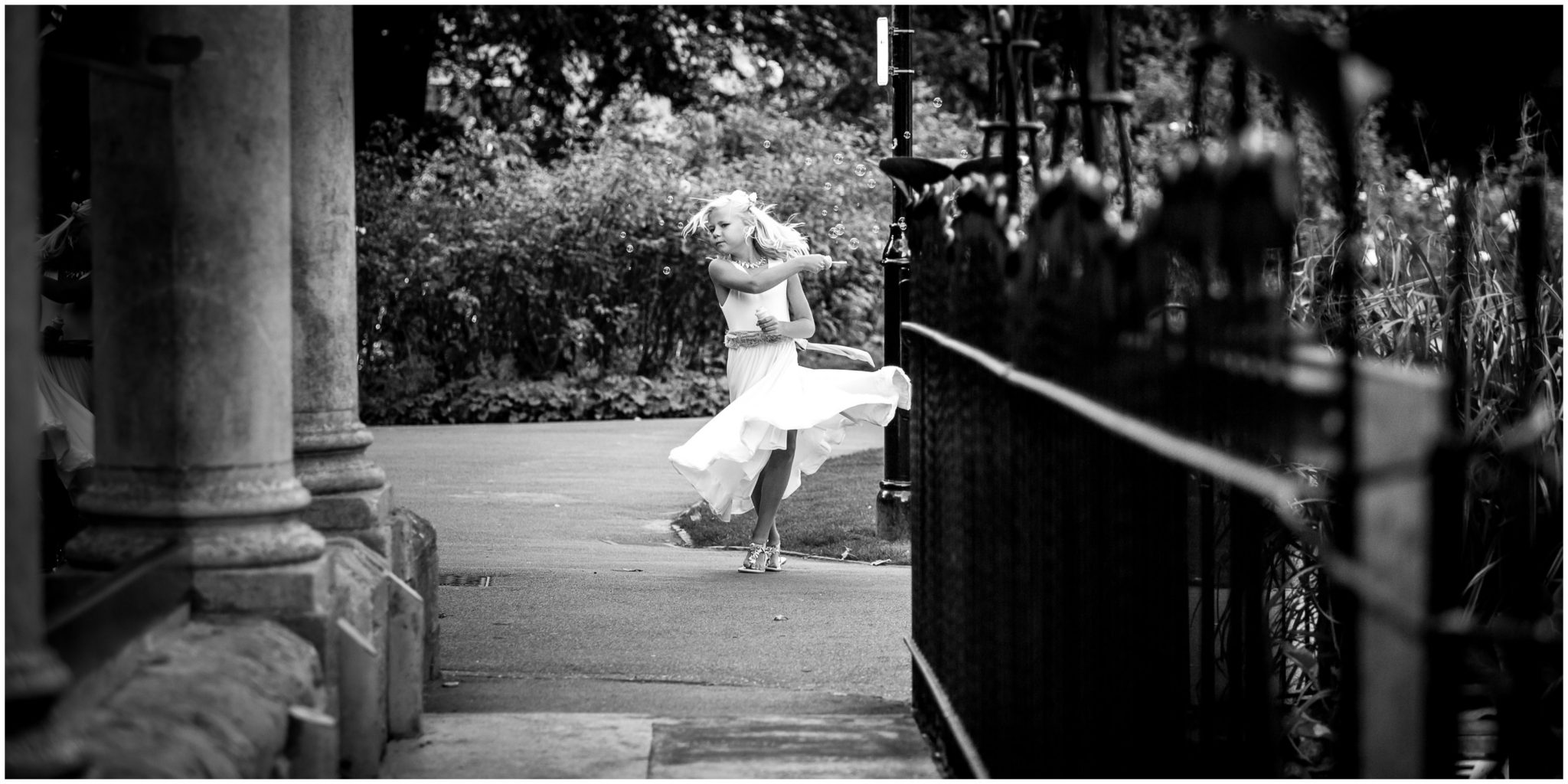 The bride's daughter and flower girl dancing in the gardens