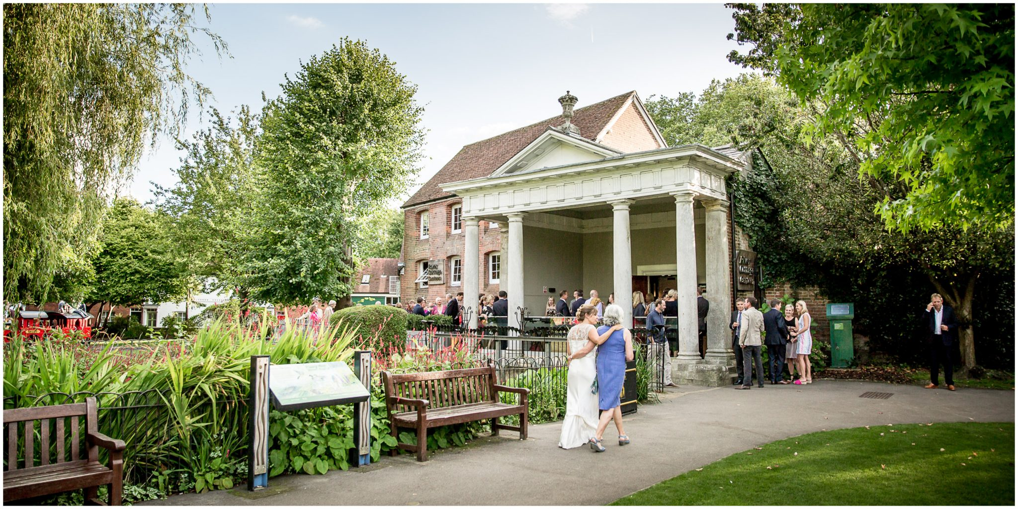 Bride and wedding guest walk towards reception venue from Abbey Gardens in Winchester