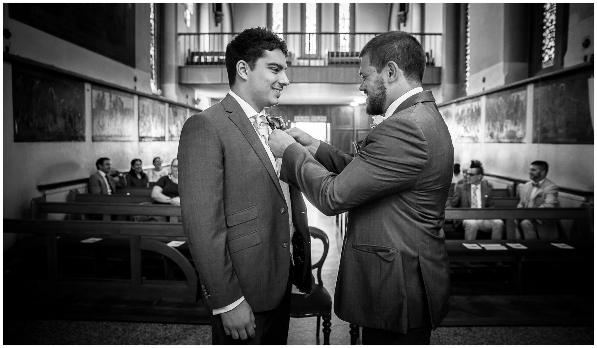 The best man adjusts the groom's tie before his bride arrives
