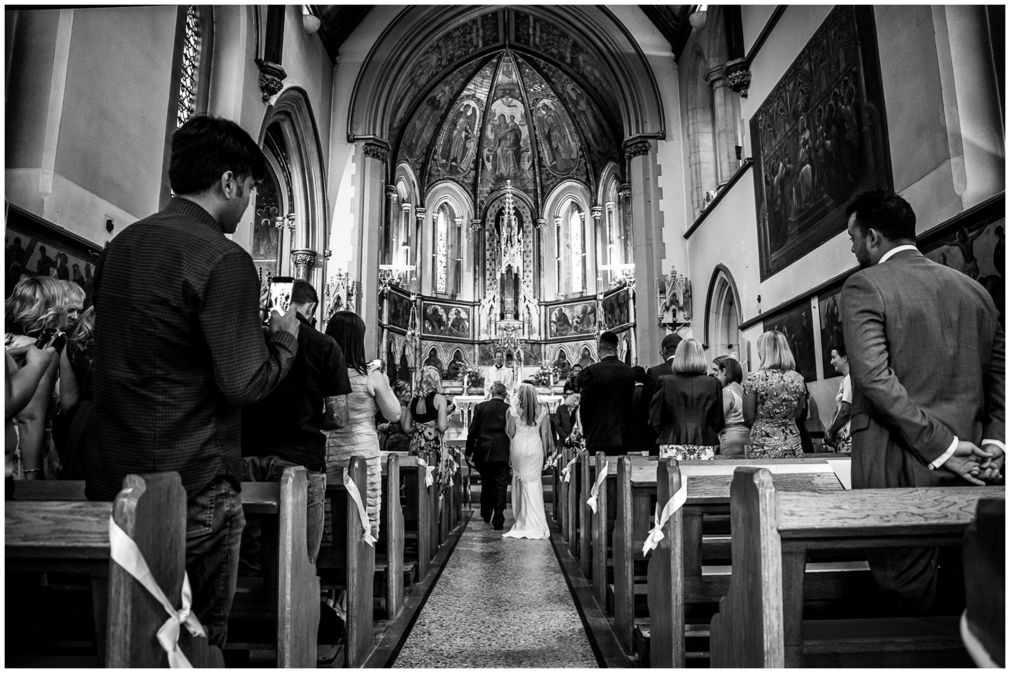 Black and white image of bride walking down aisle at start of ceremony