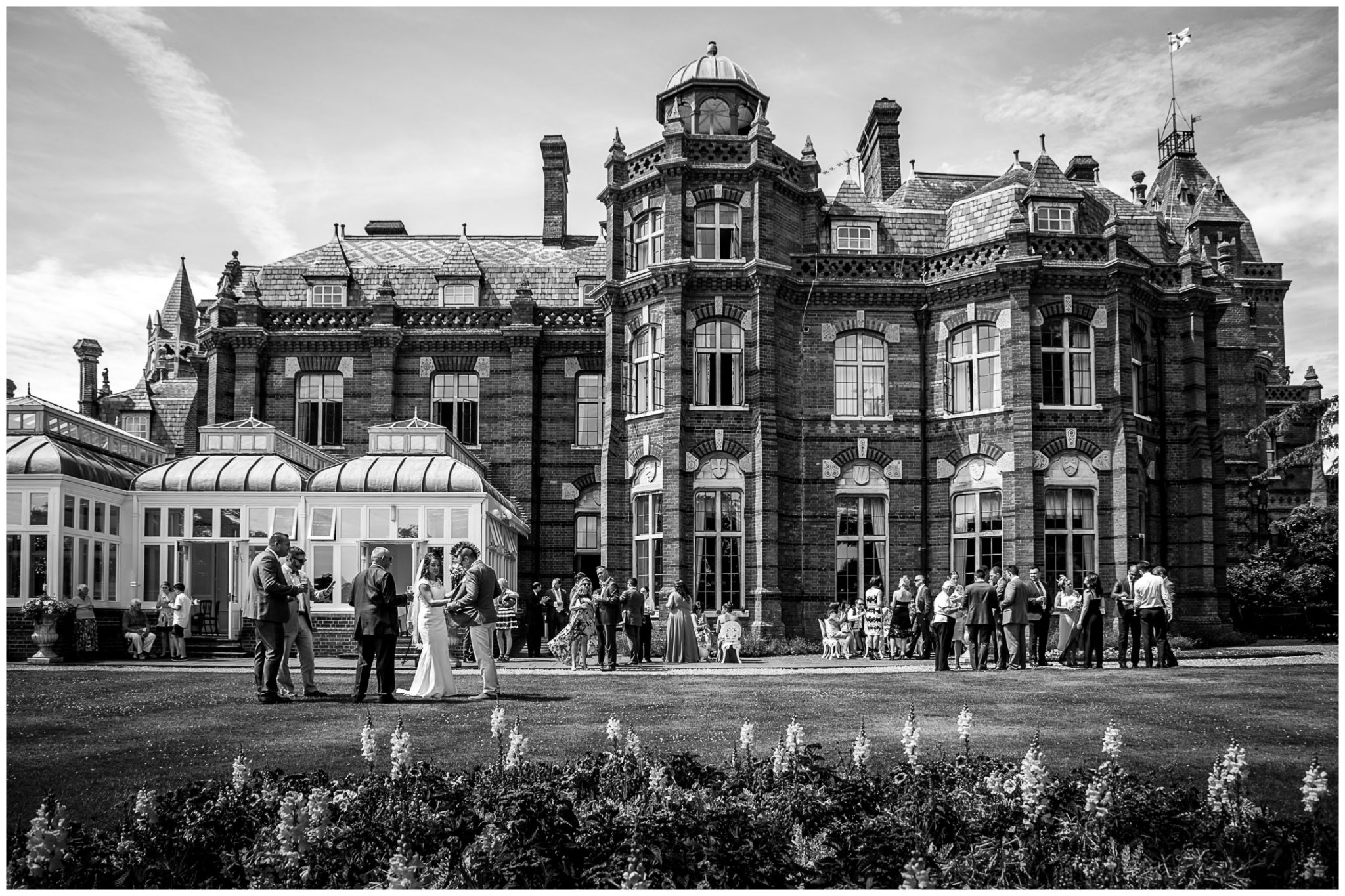 Black and white Elvetham hotel exterior with wedding guests on lawn