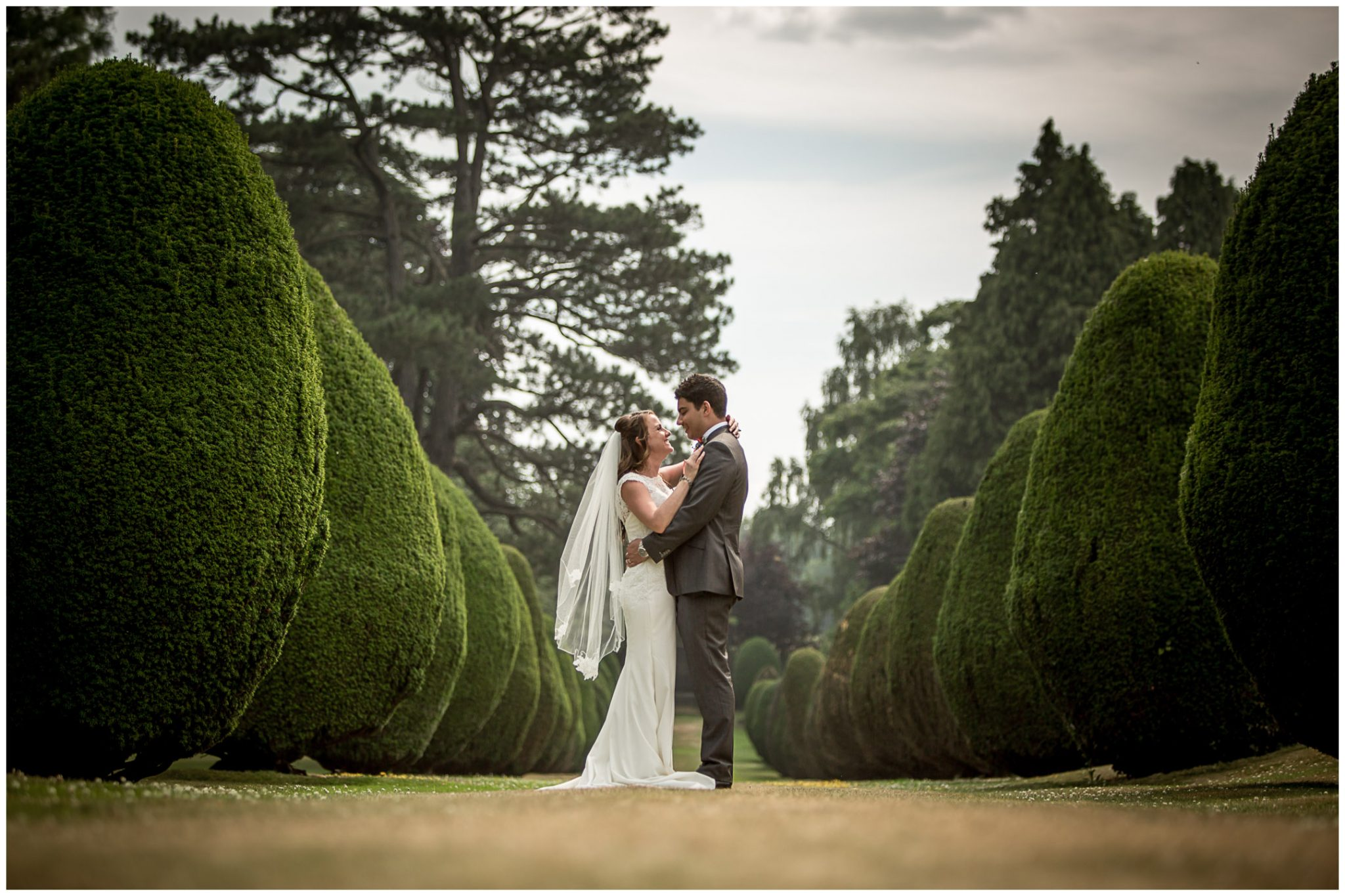 Bride and groom in hotel grounds couple portrait - tree lined avenue t The Elvetham