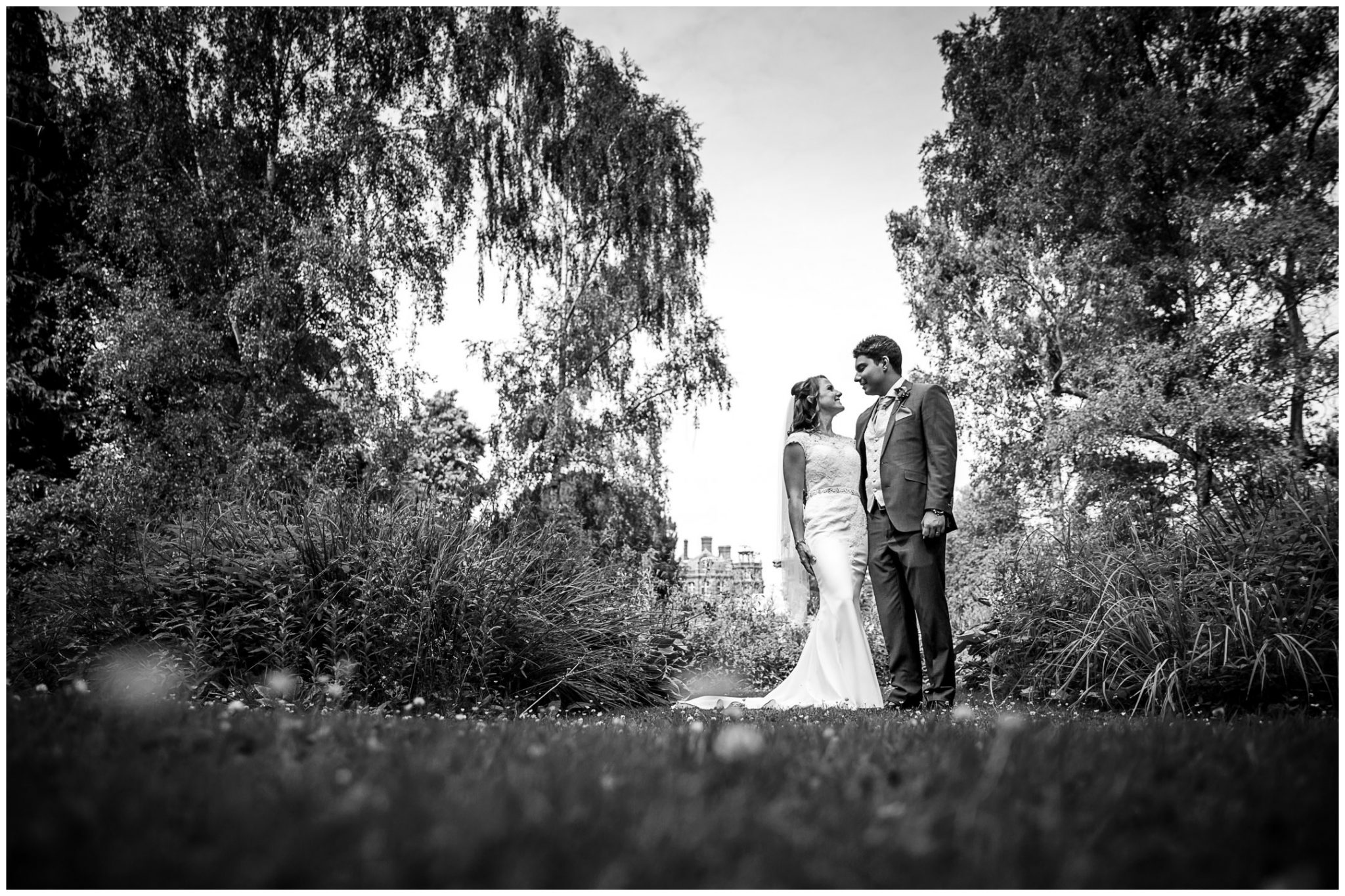 Black and white photograph of couple by the pond in formal gardens in the Elvetham hotel grounds