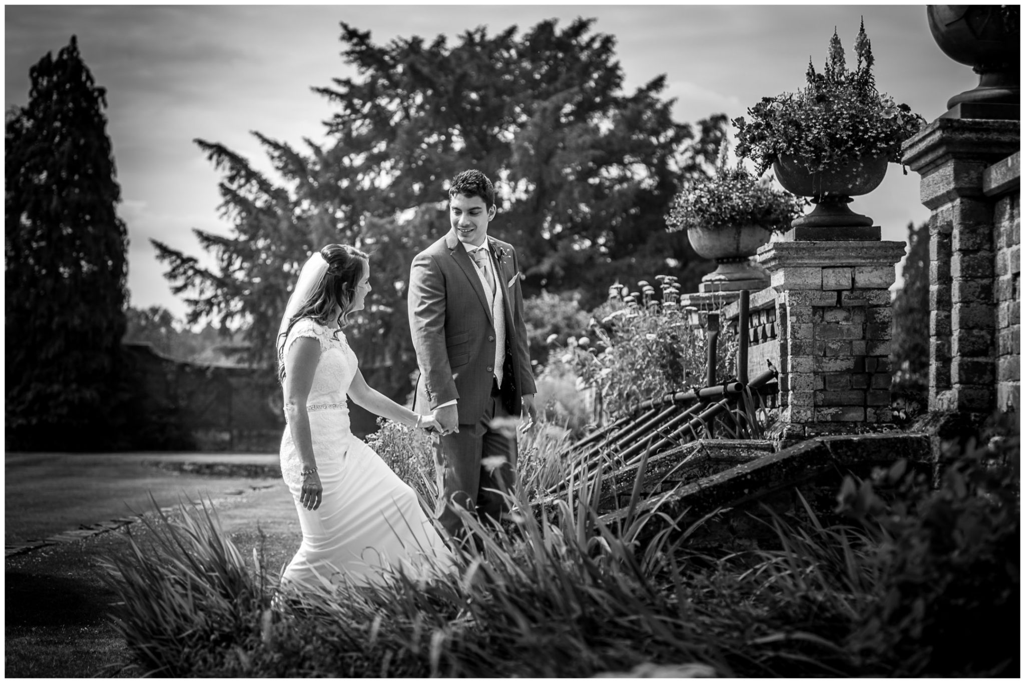 Black and white photo of couple walking through grounds of the Elvetham hotel