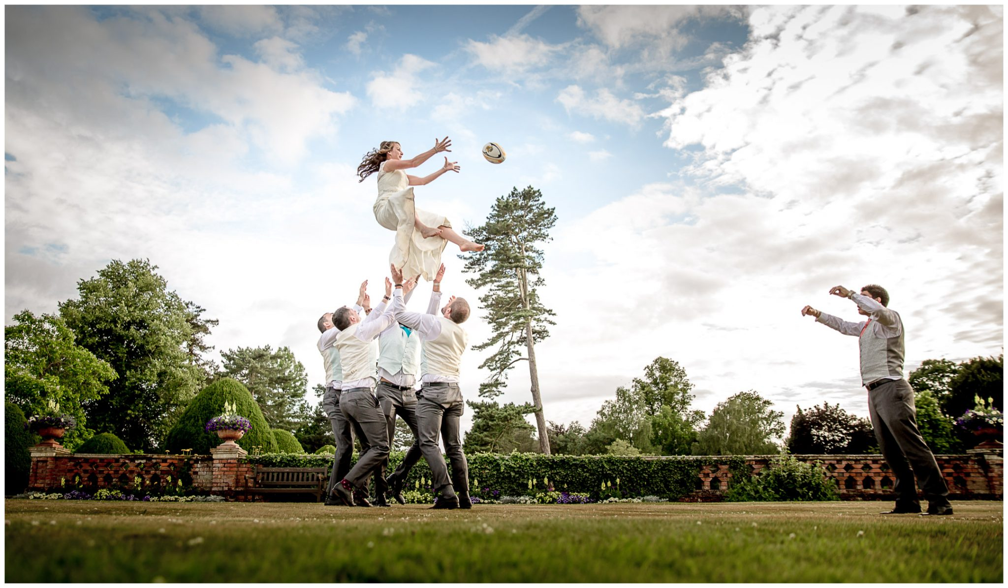 The bride is thrown in the air by the groomsmen for a line-out in the gardens of the Elvetham Hotel