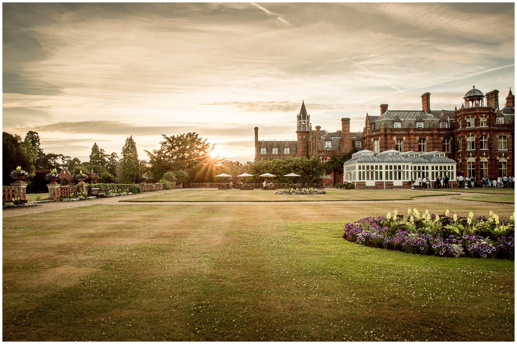Sun sets behind the trees, showing the Elvetham hotel in the evening light