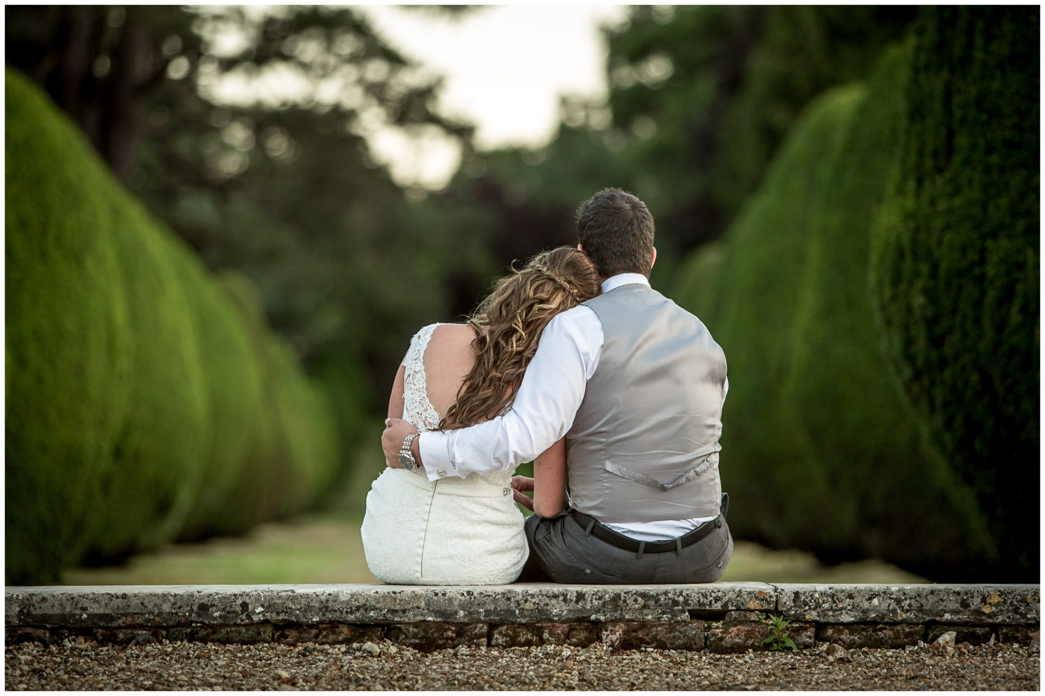 Bride and groom sat together in grounds of the Elvetham hotel