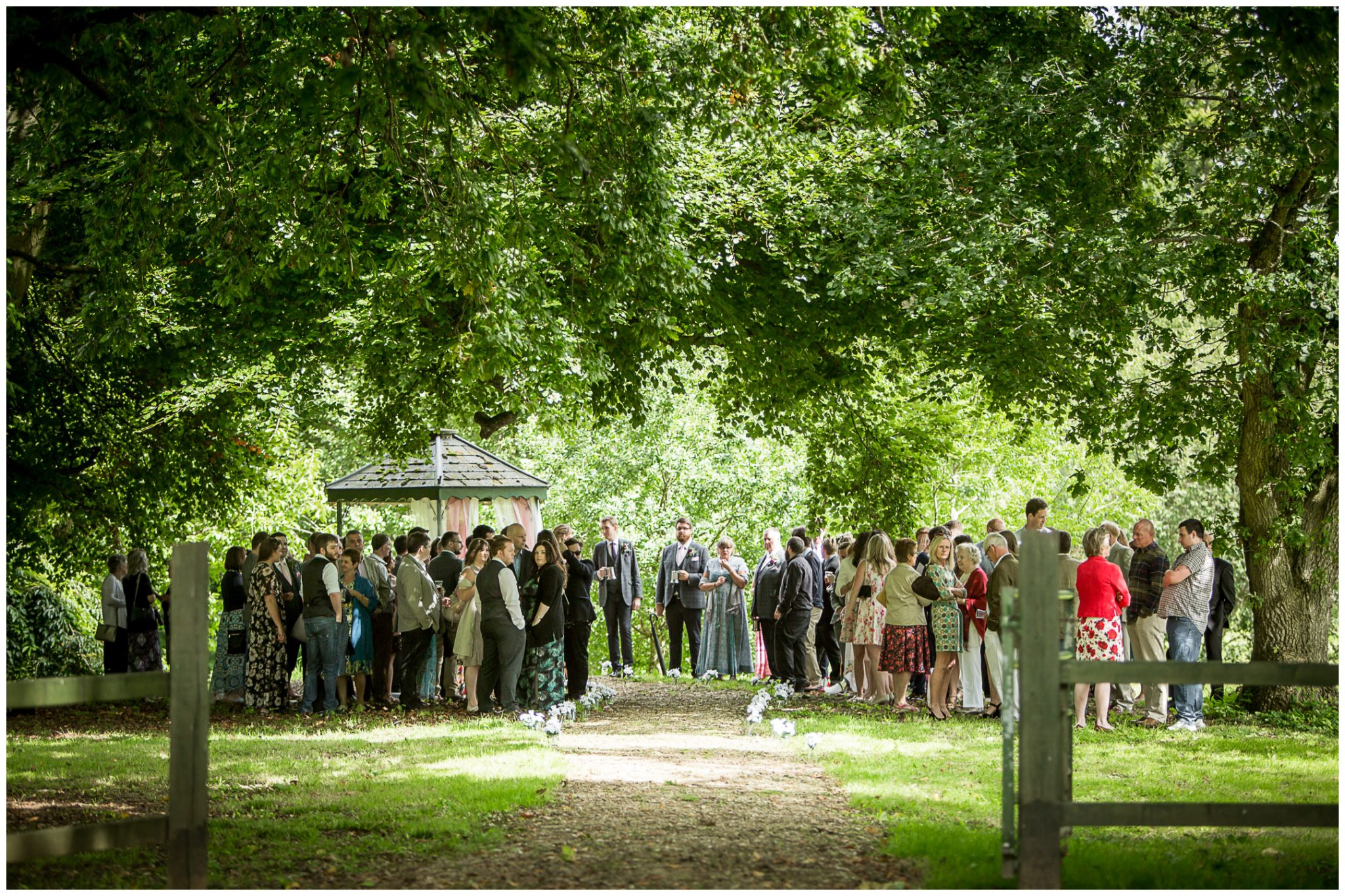 Timsbury Manor Festival Wedding guests waiting amongst the trees for start of outdoor ceremony