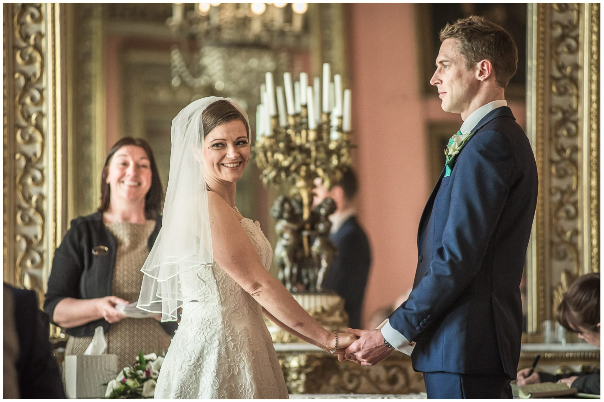 Avington Park wedding photography bride and groom hold hands during ceremony in ballroom