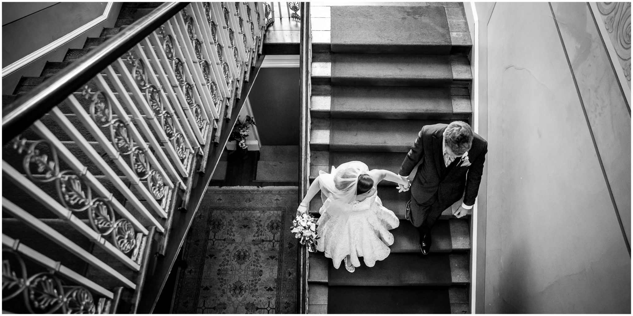 Avington Park wedding photography bride and groom walking down staircase