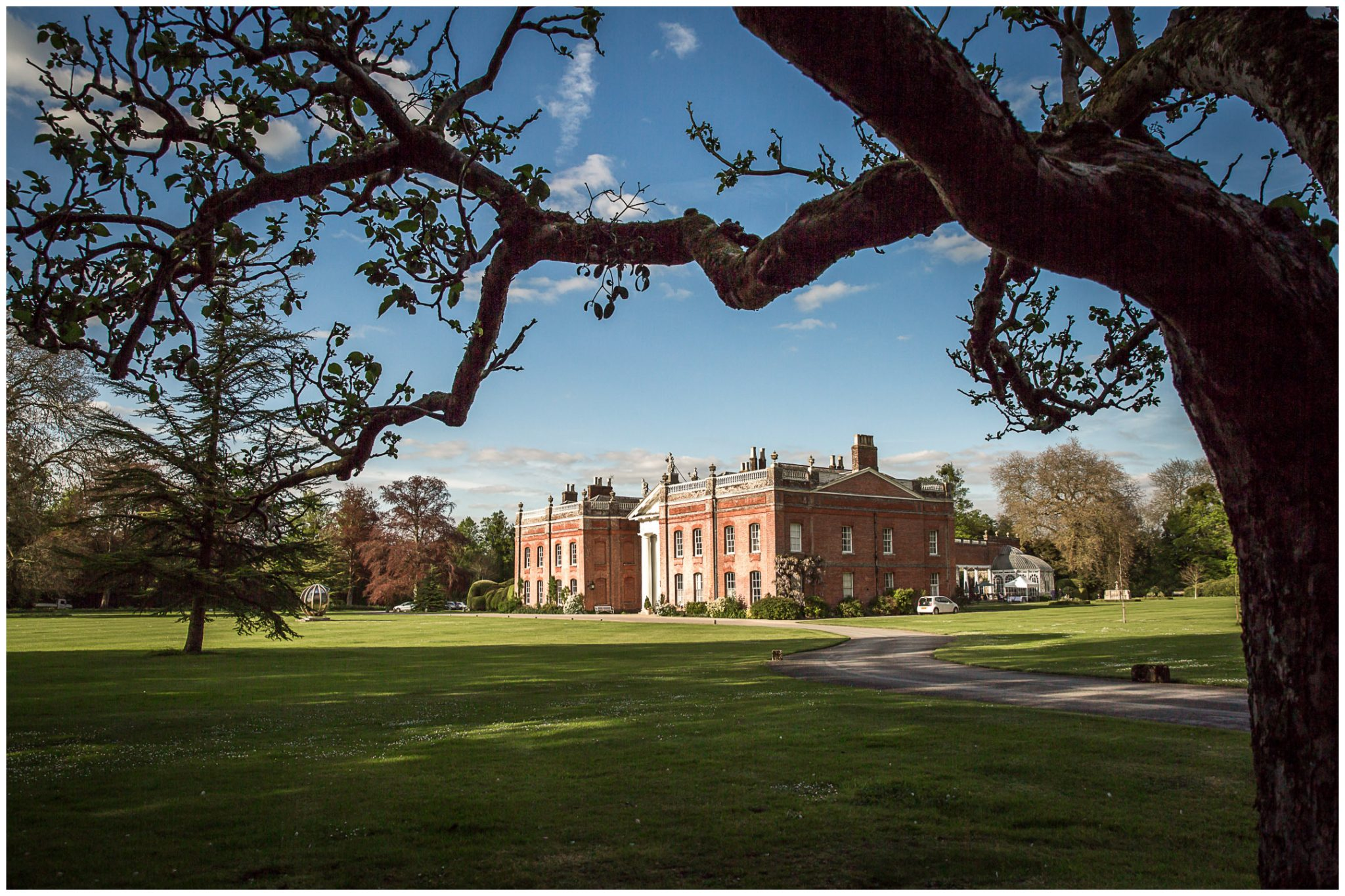 Avington Park wedding photography house view framed by trees