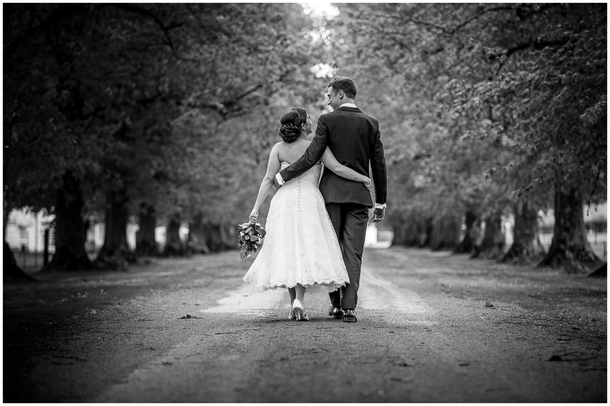 Avington Park wedding photography bride and groom walk along avenue