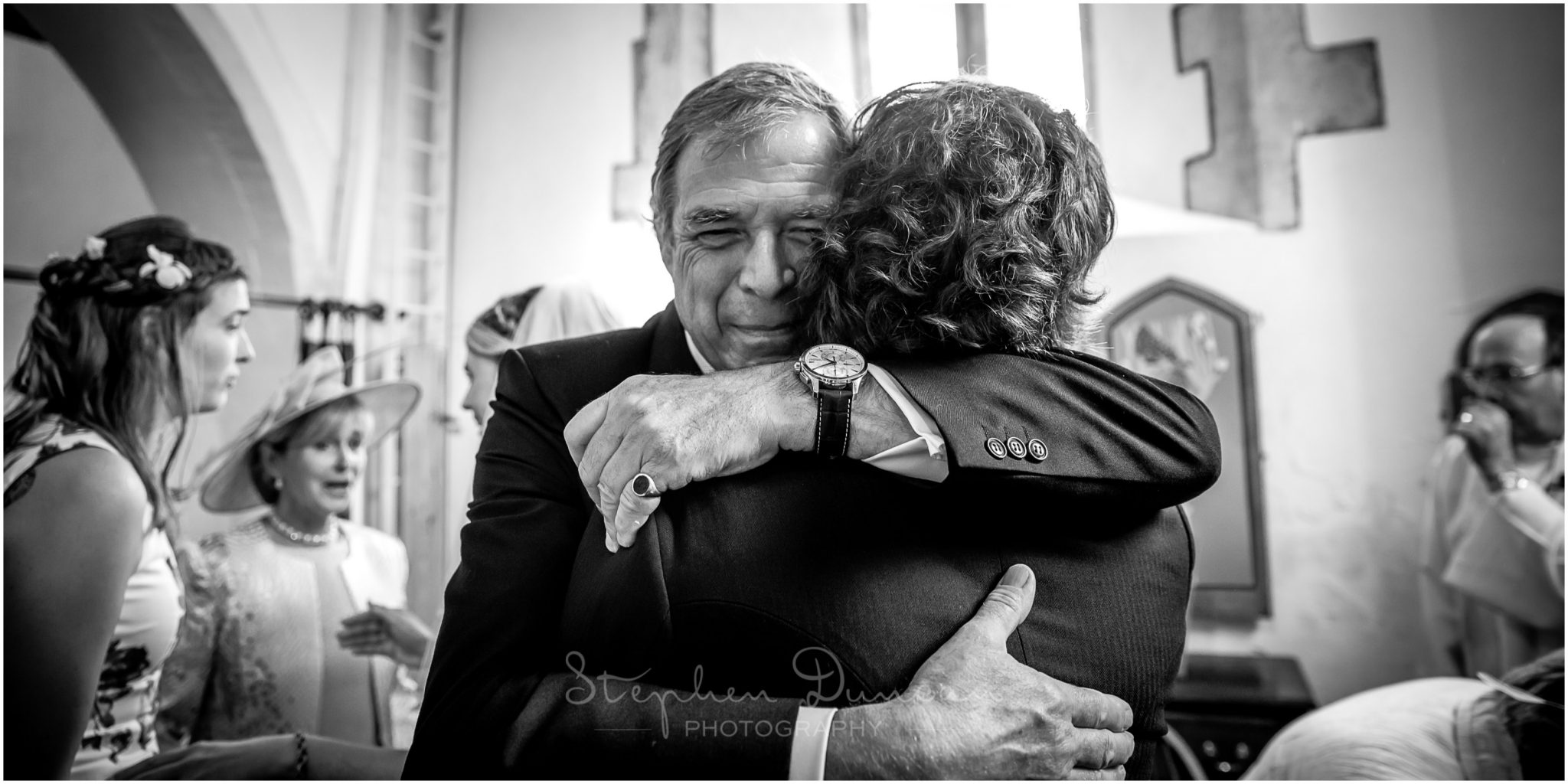 Lymington wedding photography groom hugs father in law