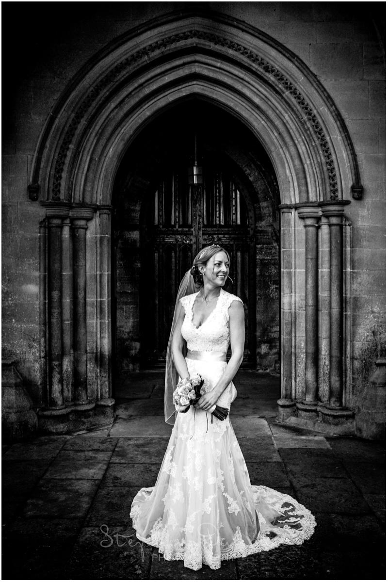Romsey Abbey wedding photographer bride stands in doorway